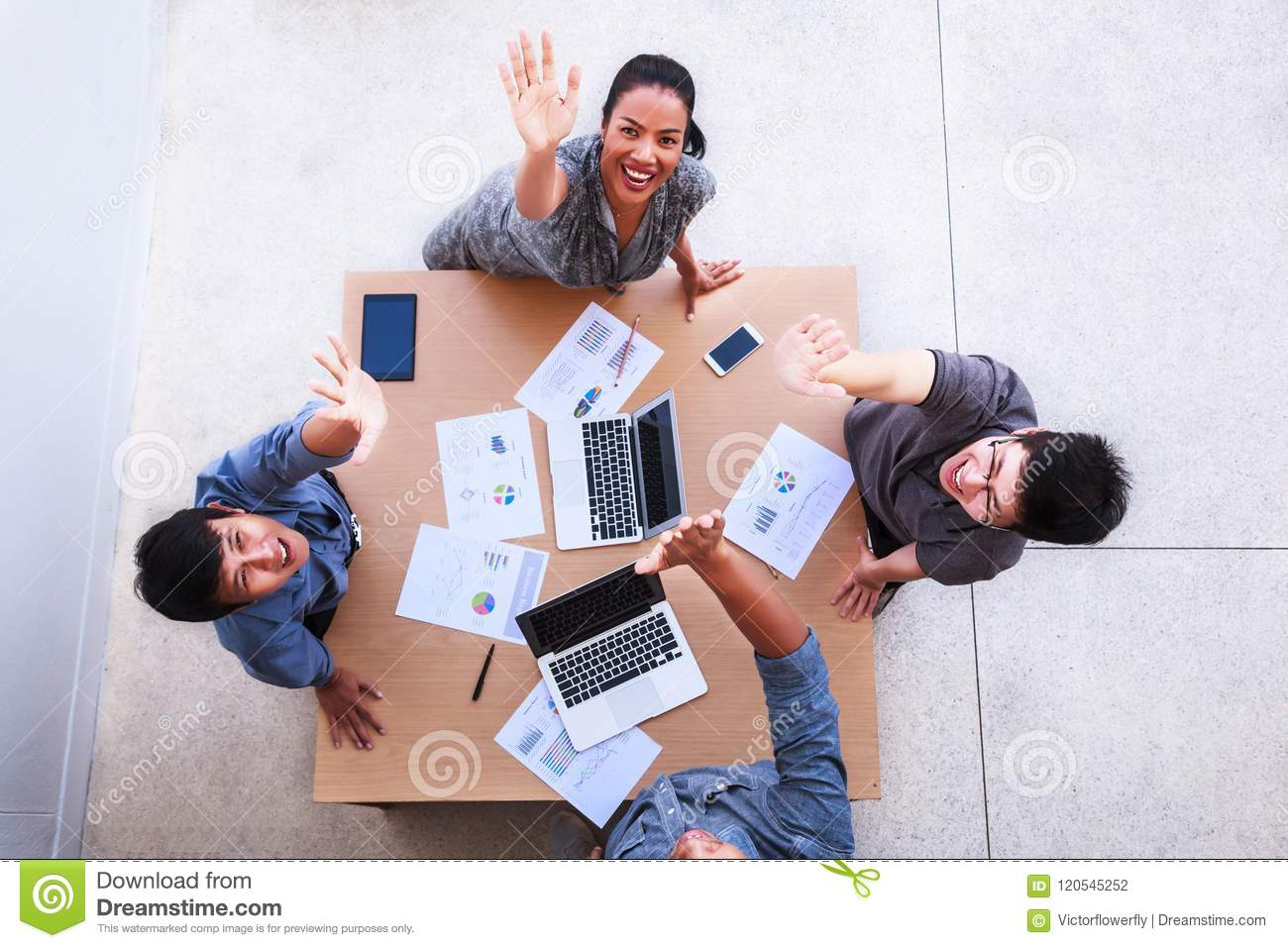 Top view of businessmen and businesswoman celebrate over table in a meeting with copy space at mobile office. Teamwork, diversity