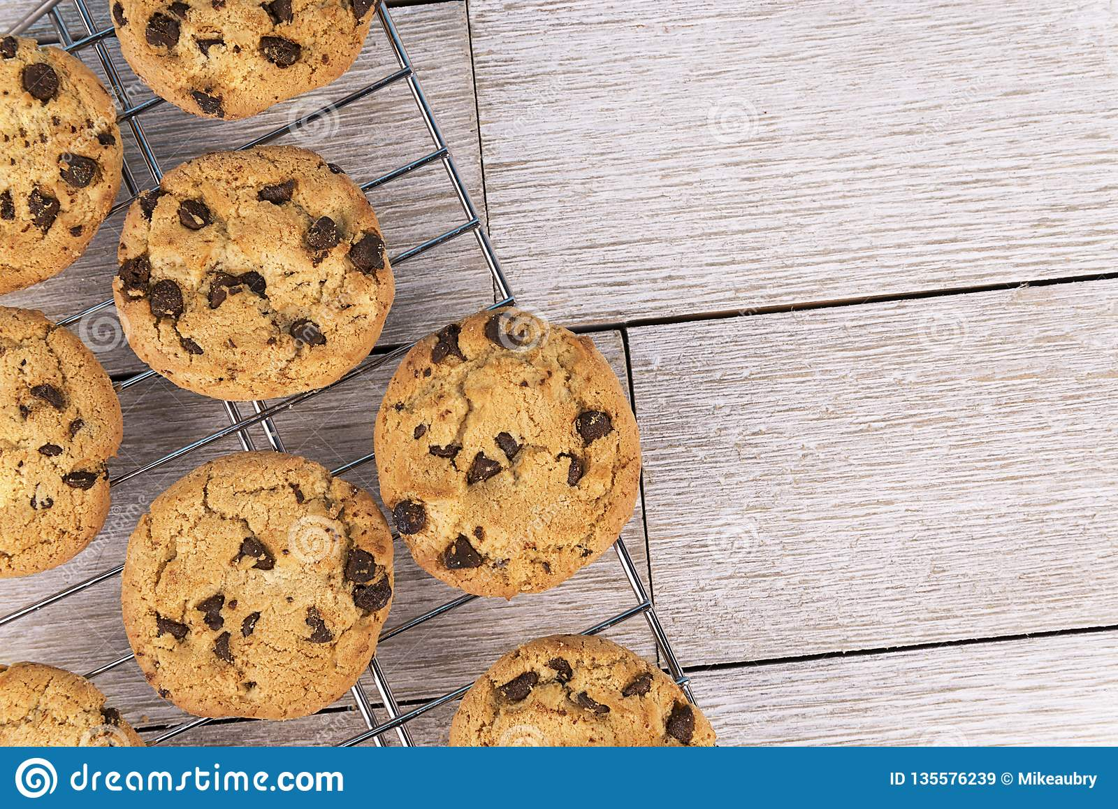 Top view of chocolate chip cookies on a cooling rack, white wooden plank in background.