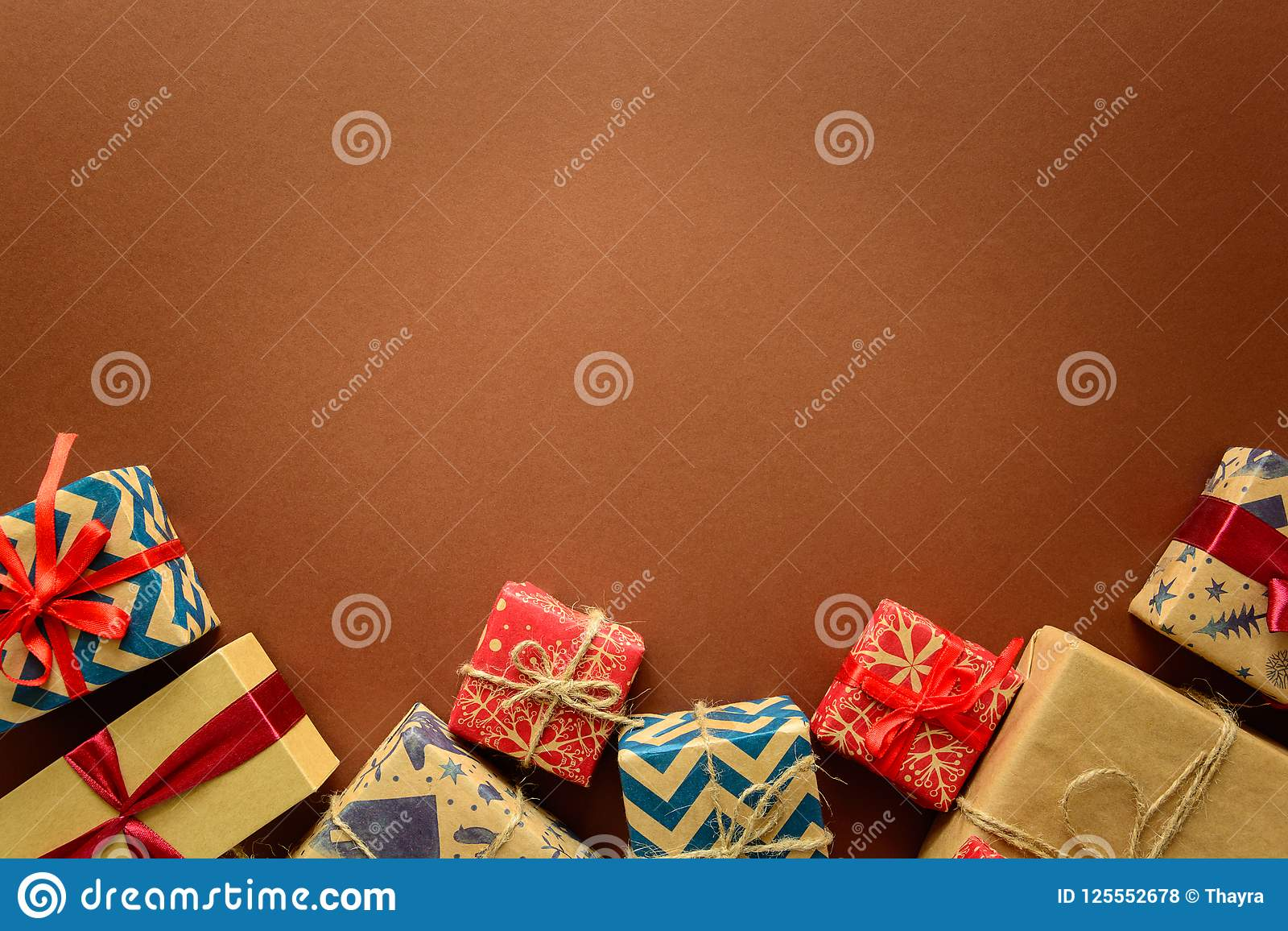 Top view on Christmas gifts wrapped in gift paper decorated with ribbon on brown paper background.