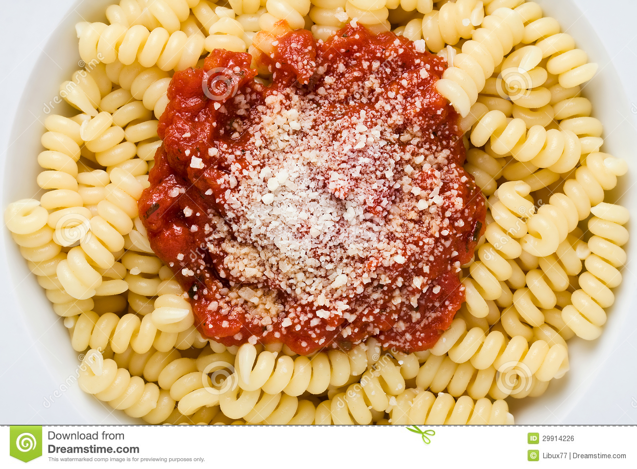 Top view close up of pasta with tomato sauce and parmesan cheese.