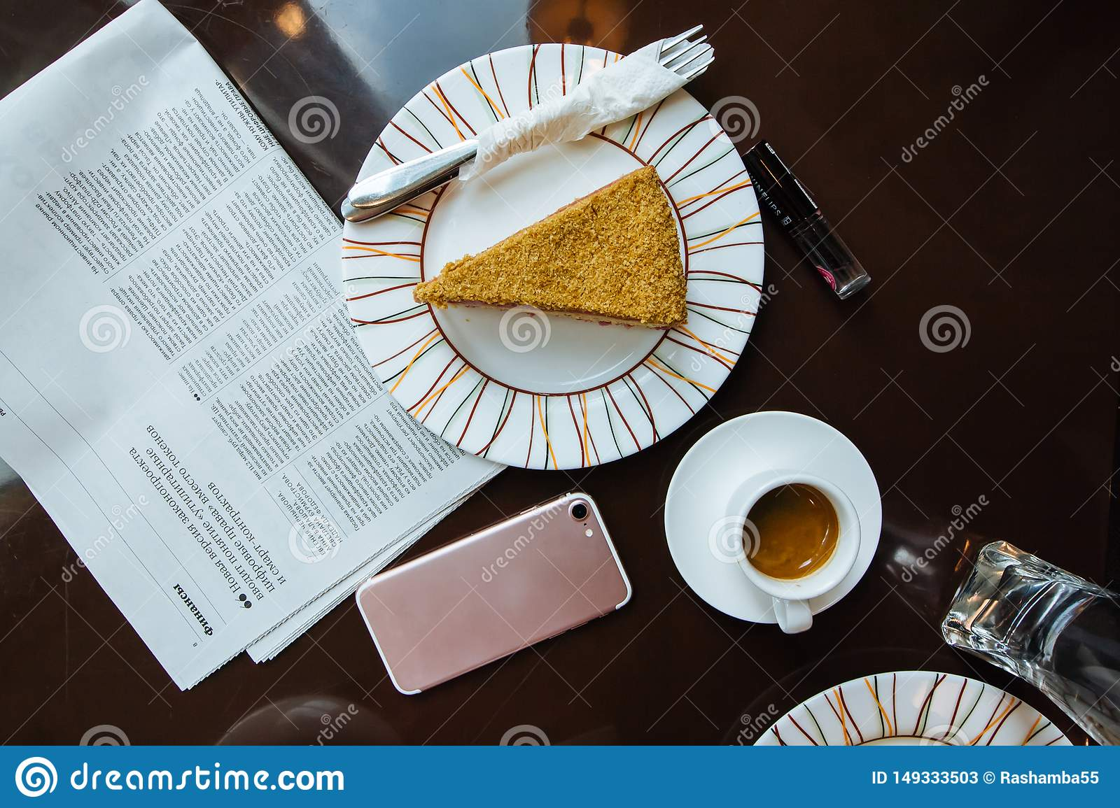Top view Coffee served with cake, newspapper an cellphone on the dark brown table