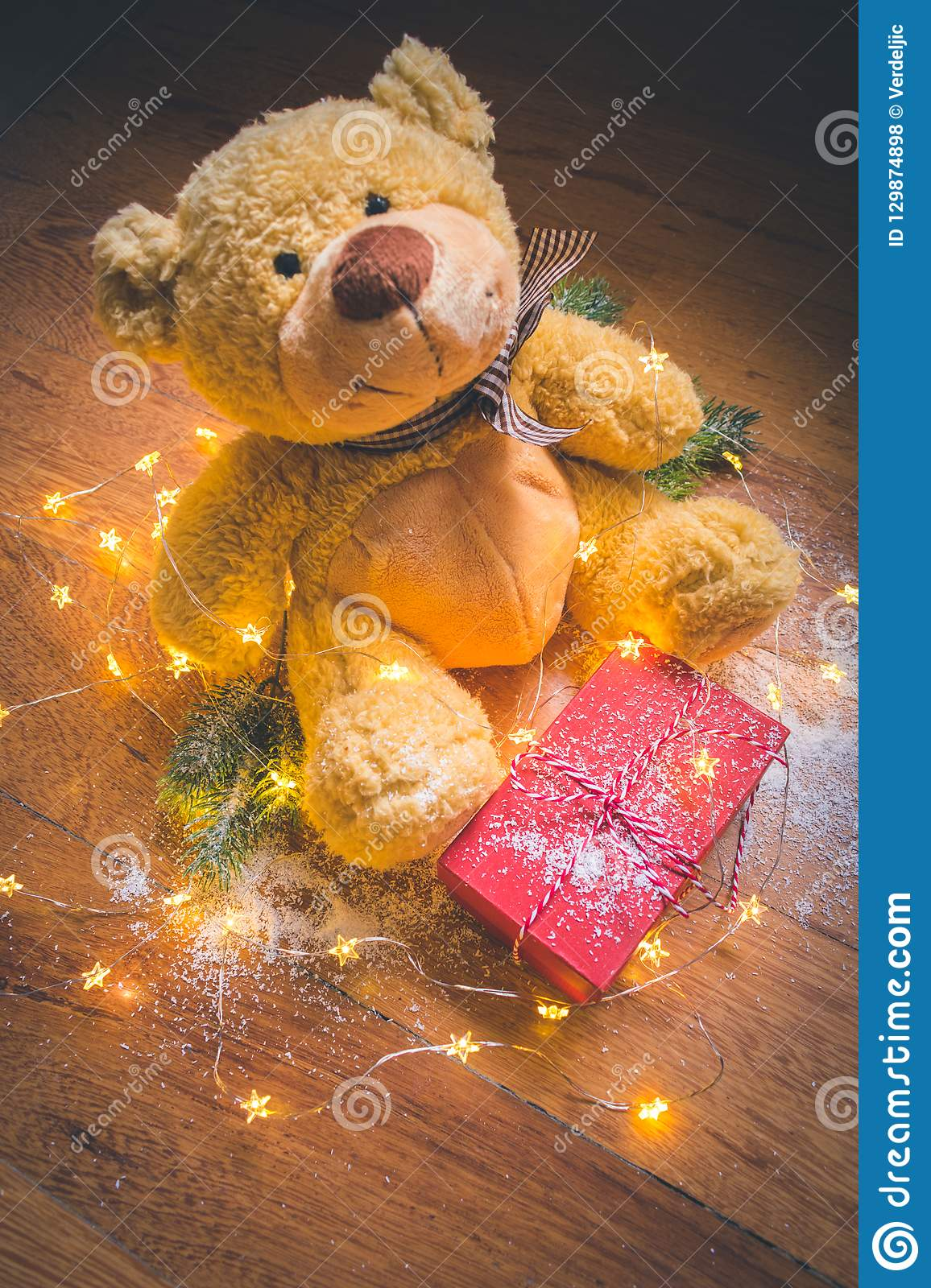 View of a teddy with a red wrapped present, and Christmas decorations on wooden background