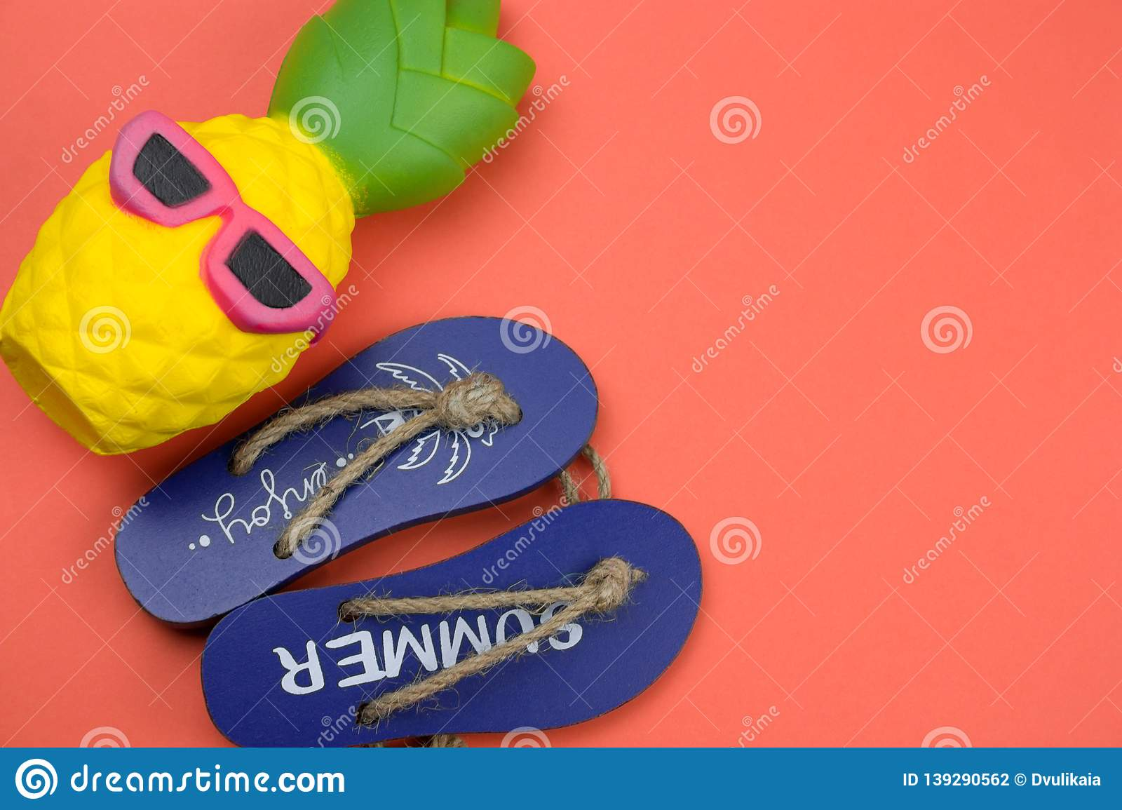 2e2cc76a434 decorative wooden flip flops and squishy toy pineapple on a coral  background copy space