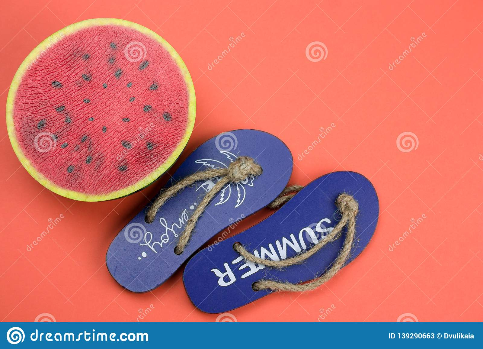 9990b2bbbb30 decorative wooden flip flops and squishy toy watermelon on a coral  background copy space