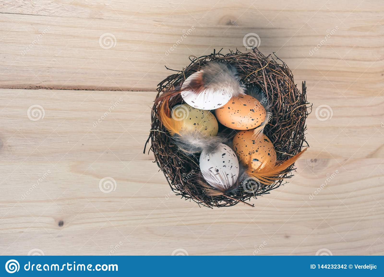 Top view of an Easter nest with orange, brown and white quail eggs decorations with feathers on wooden background