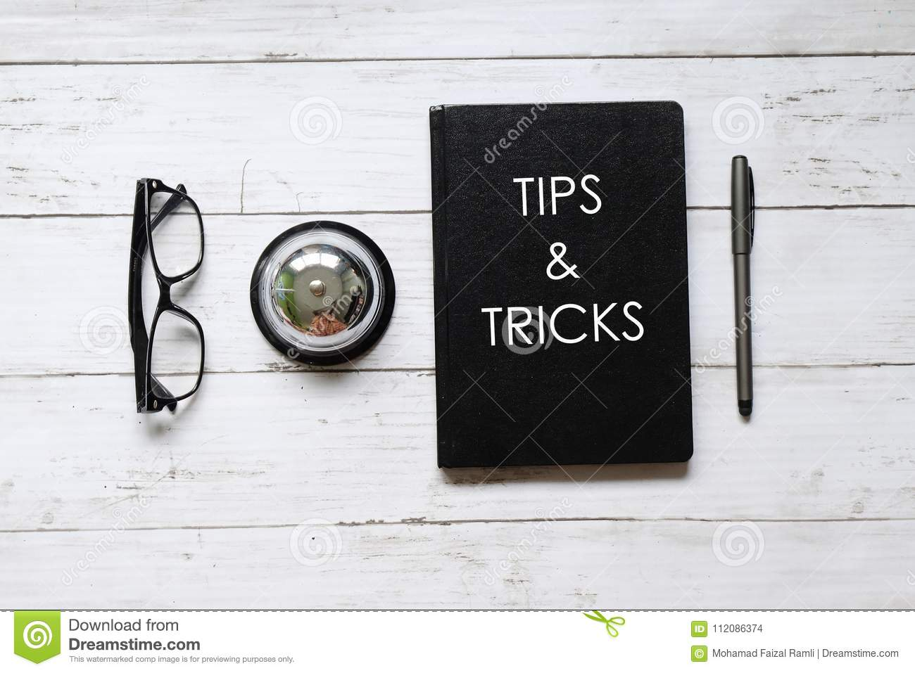 Top view of eyeglasses, ring bell,pen and notebook written with TIPS & TRICKS on white wooden background