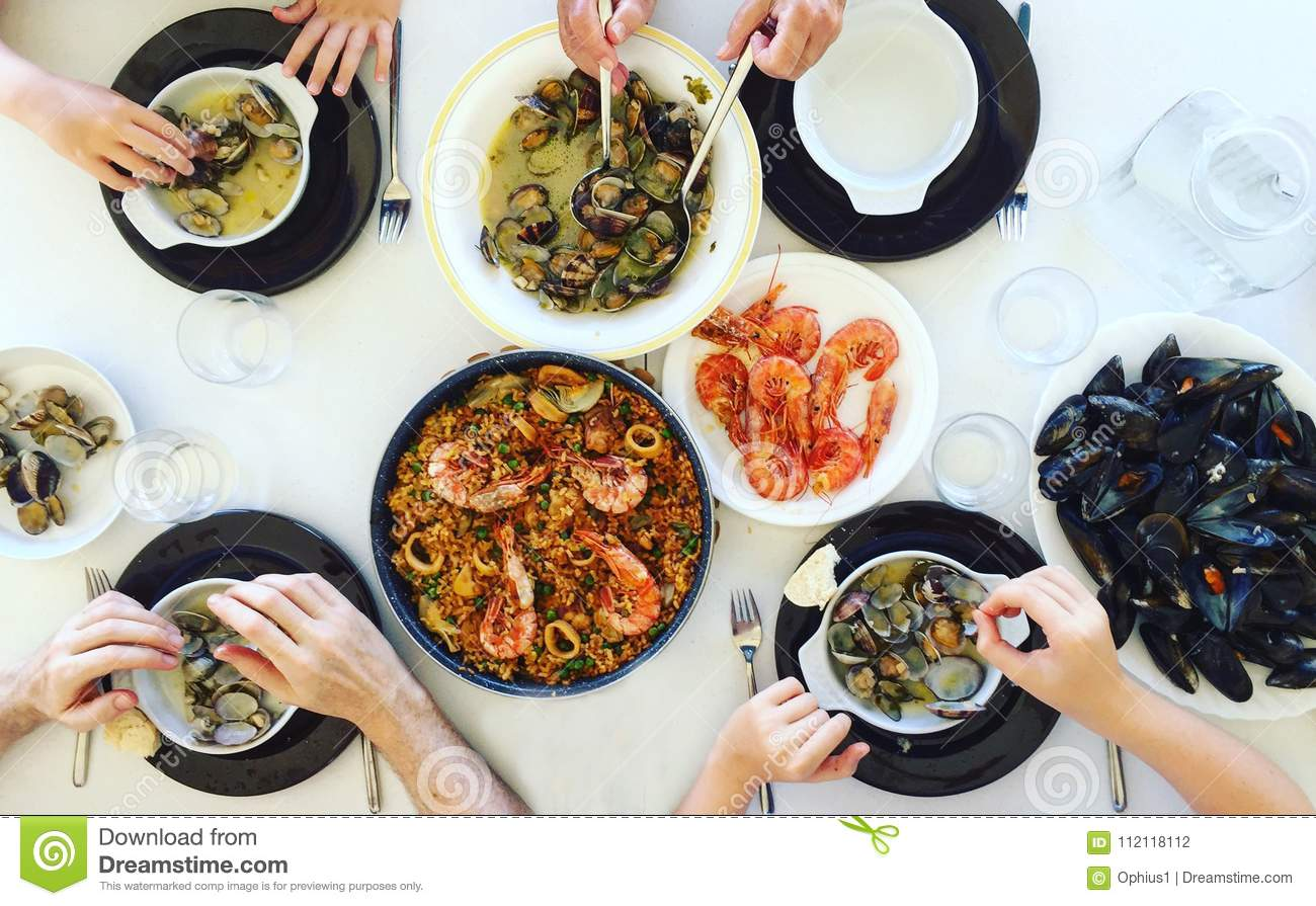 Top View Of Family Eating Paella And Seafood Around A White