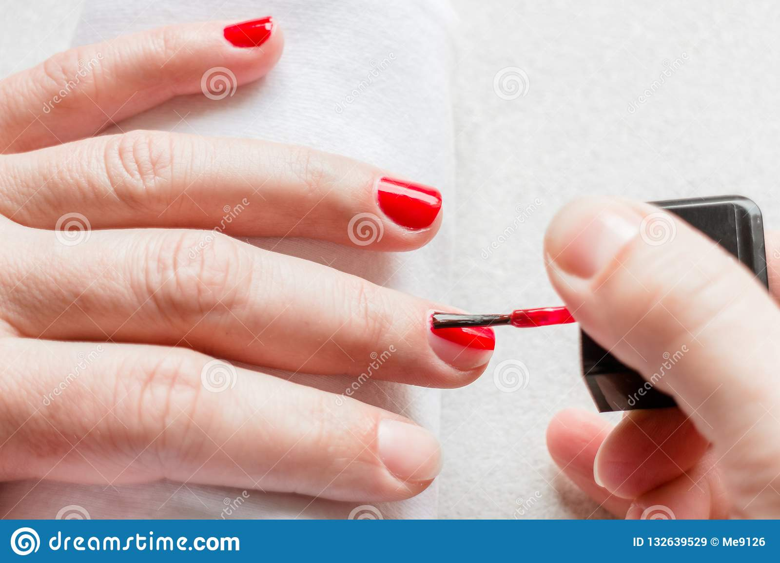 Female Hand Polishing Nails With Red Nail Polish Stock Image - Image ...