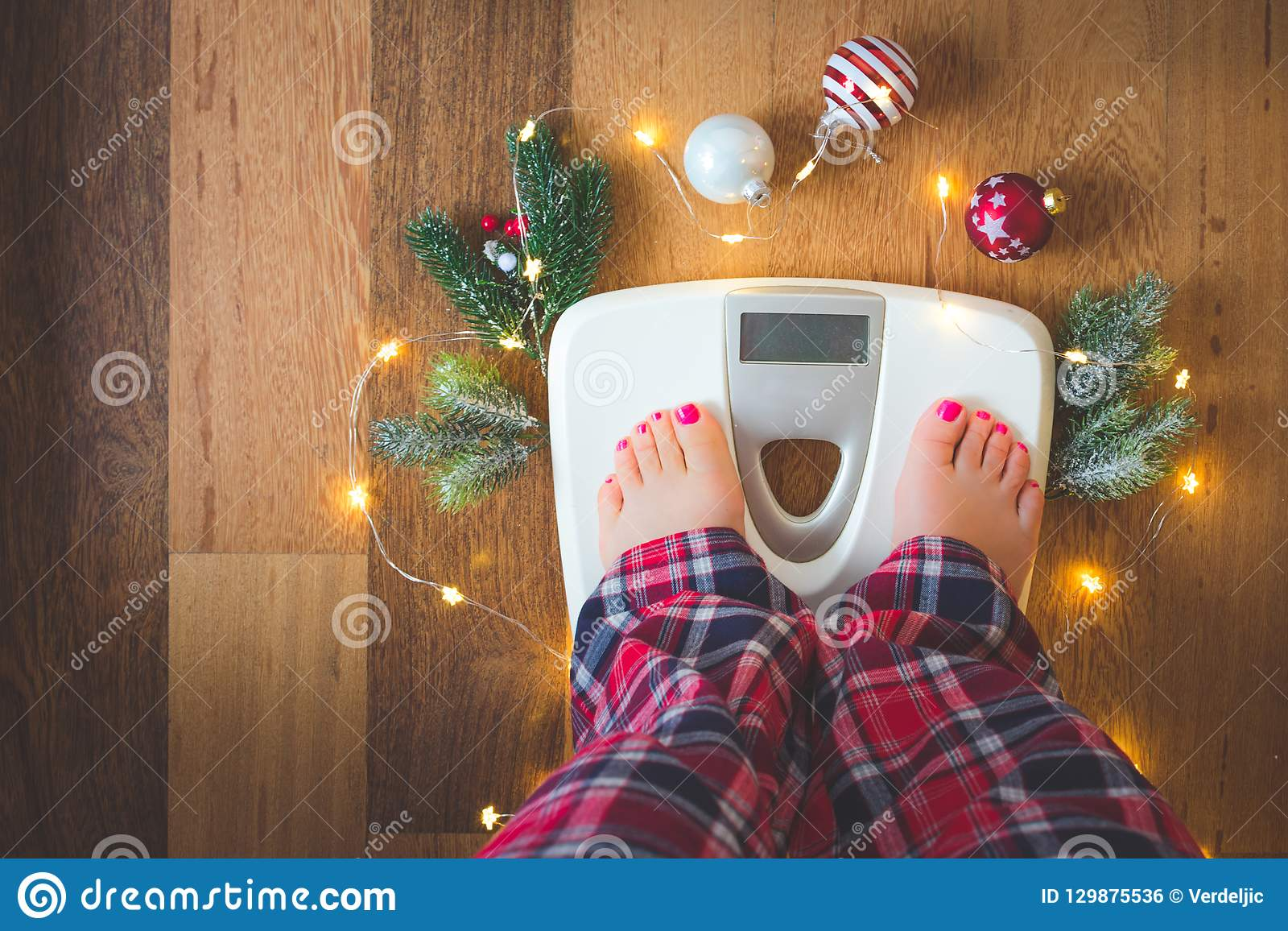 Top view of female legs in pajamas on a white weight scale with Christmas decorations and lights on wooden background