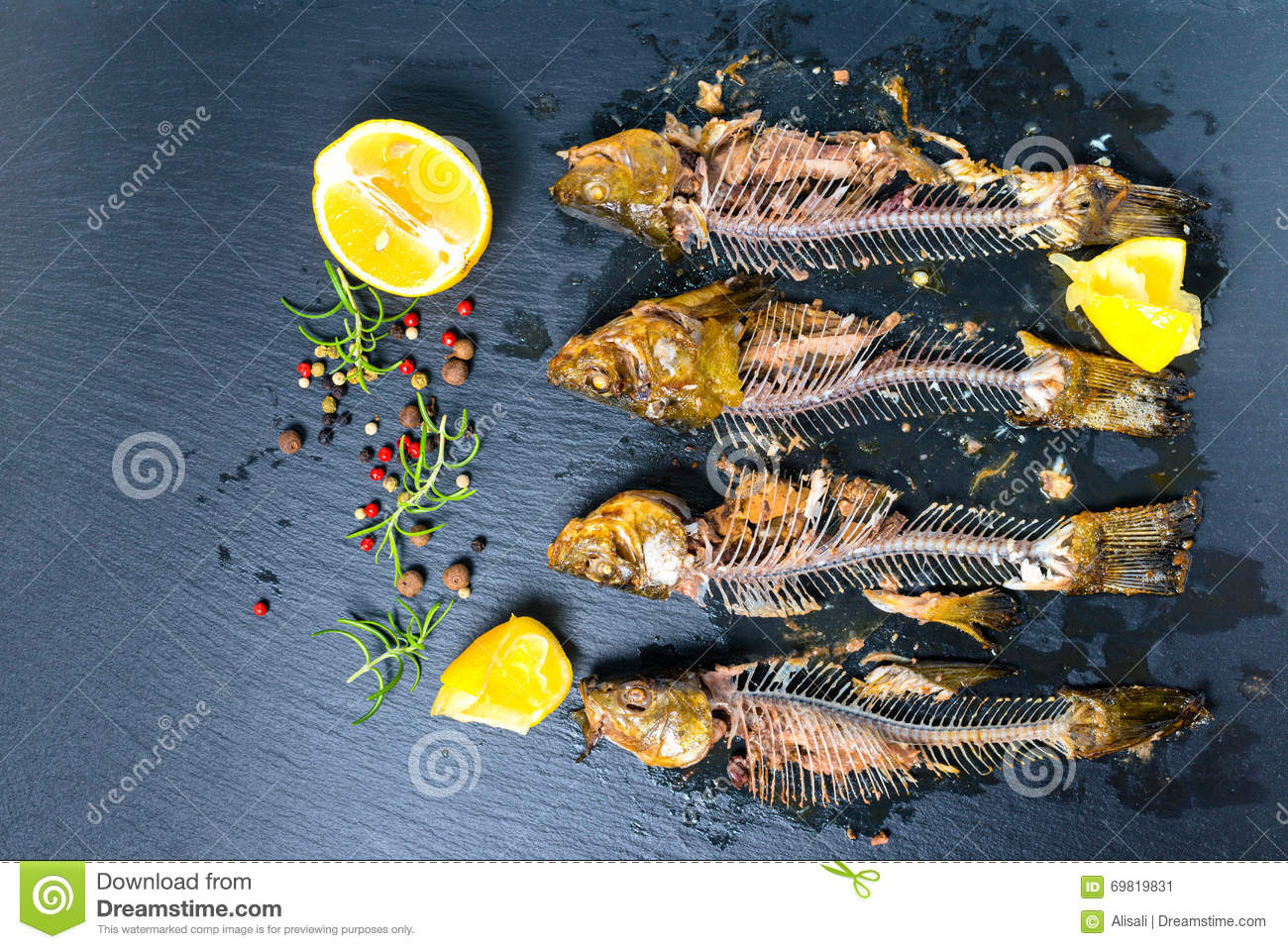 Top view of fish skeleton bones, squeezed lemon and flavor peppe