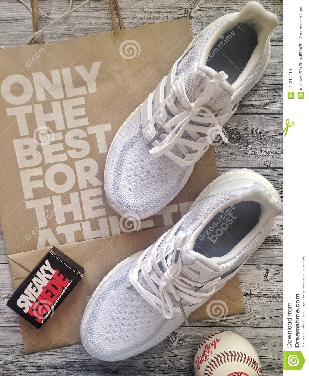 0bb5249e2 On the grey wooden table white sneakers Ultraboost with bag from adidas and baseball  ball