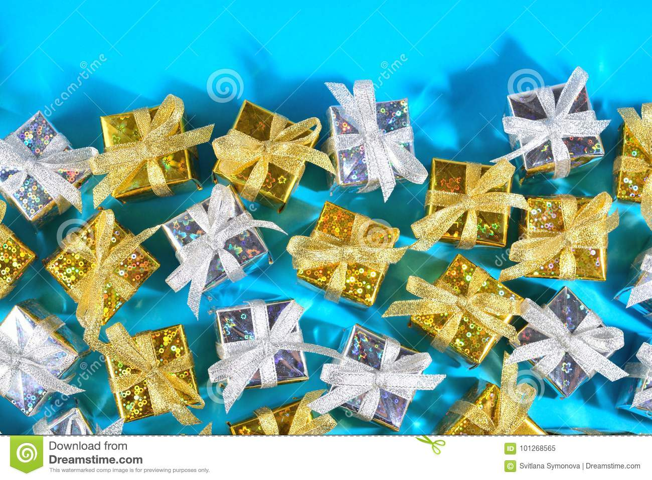 Top view of golden and silver gifts close-up on a blue