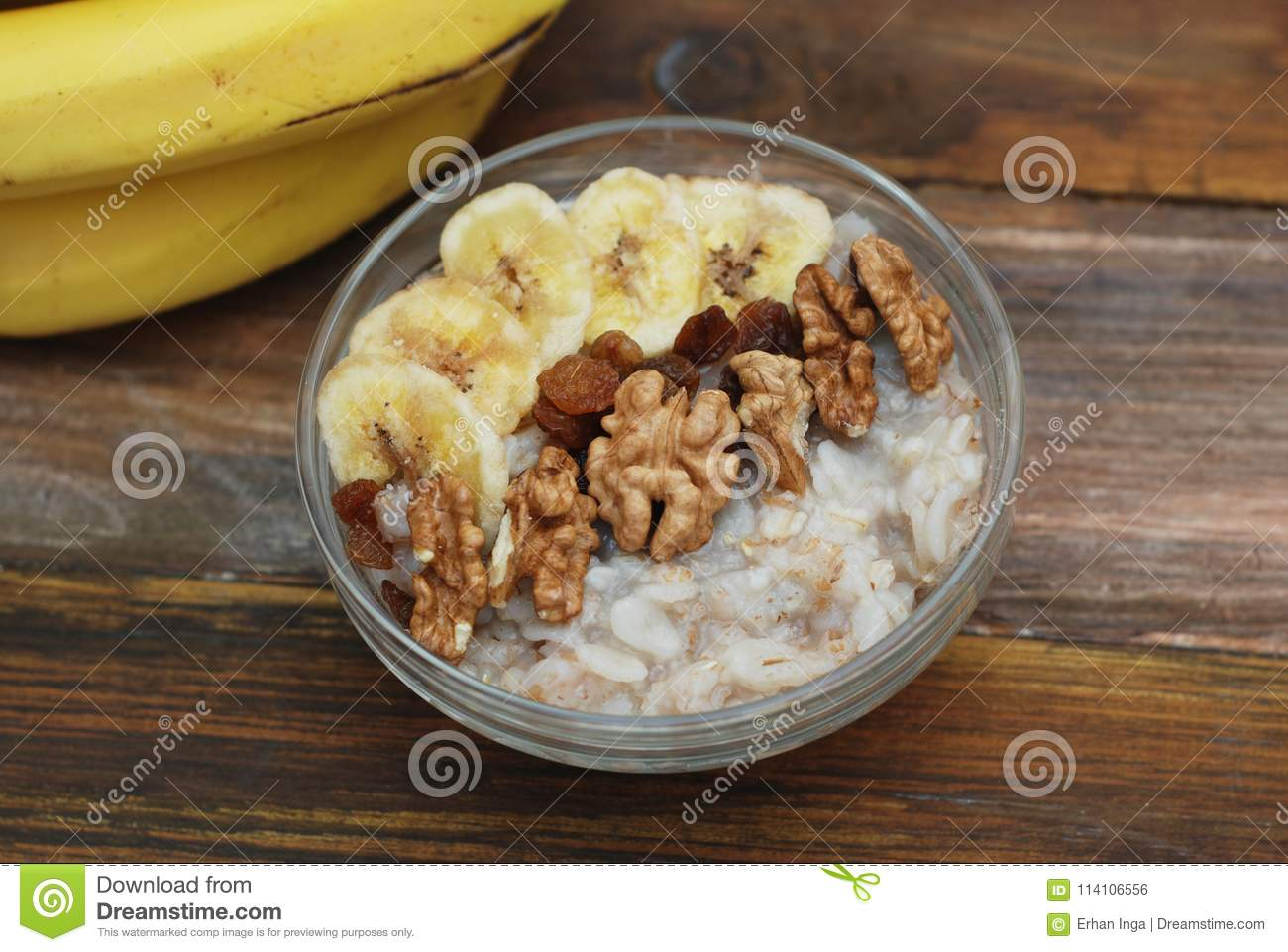 Top view of a Granola Bowl, Muesli with Oats, Nuts and Dried Fruit on Wooden table. Bannana, nuts, fruits. Healthy Breakfast. Diet