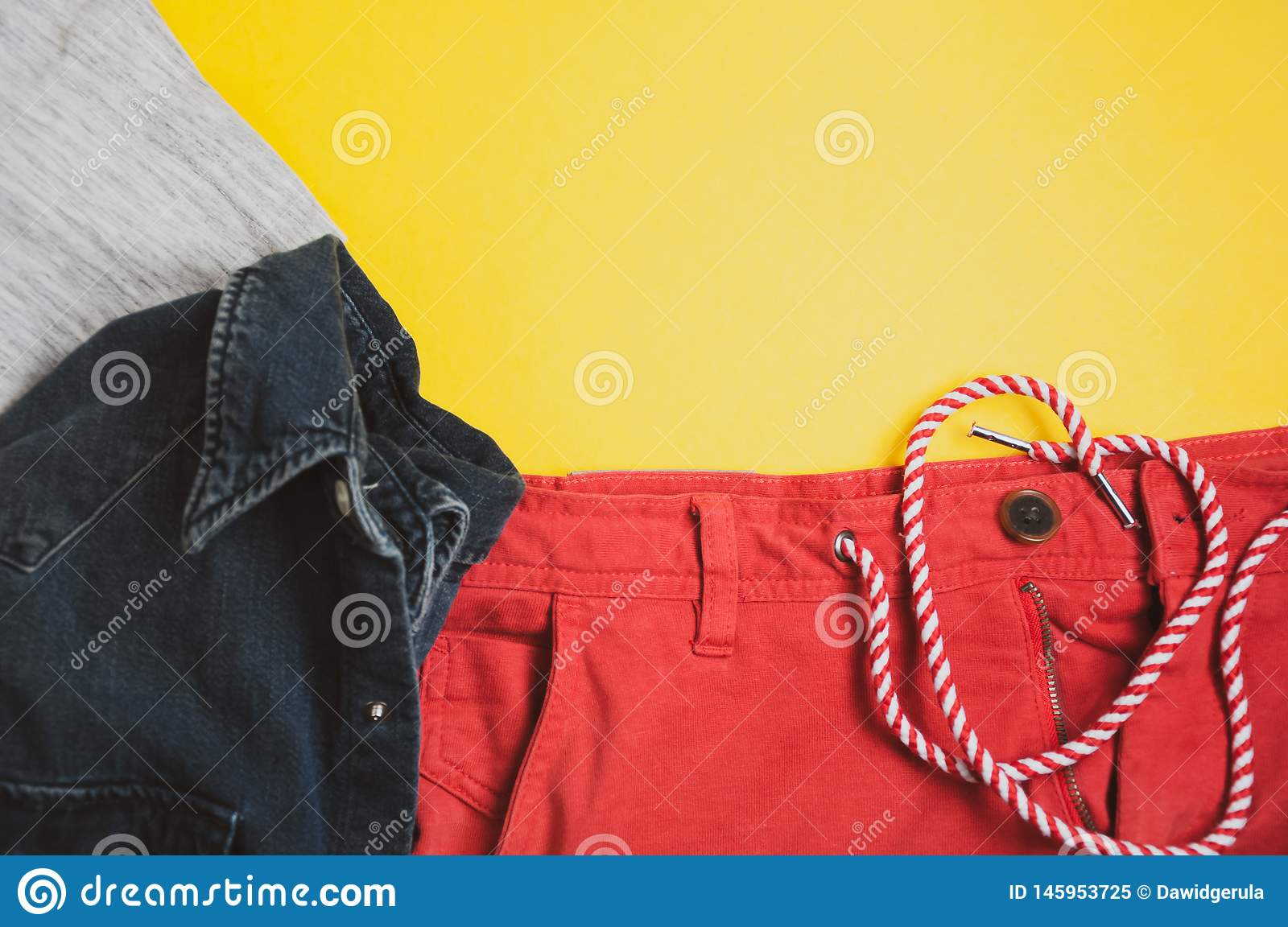 Top view of grey tshirt, denim jacket and red shorts on yellow background