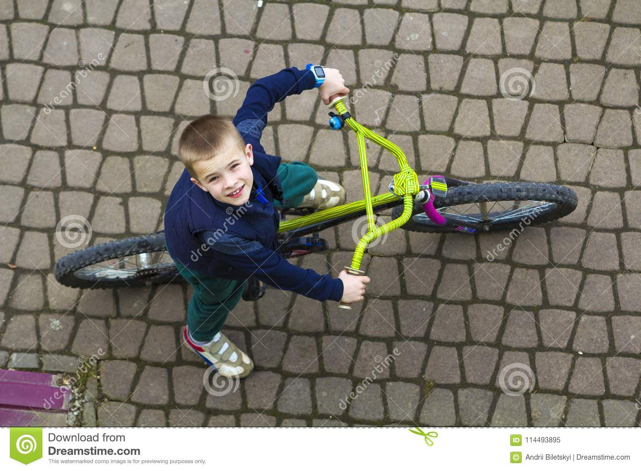 Top view of handsome young smiling boy riding a bicycle on cool spring day looking upward. Outdoors activities.healthy lifestyle a