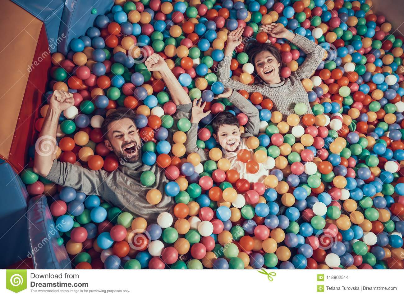 Top view. Happy family lying in pool with balls