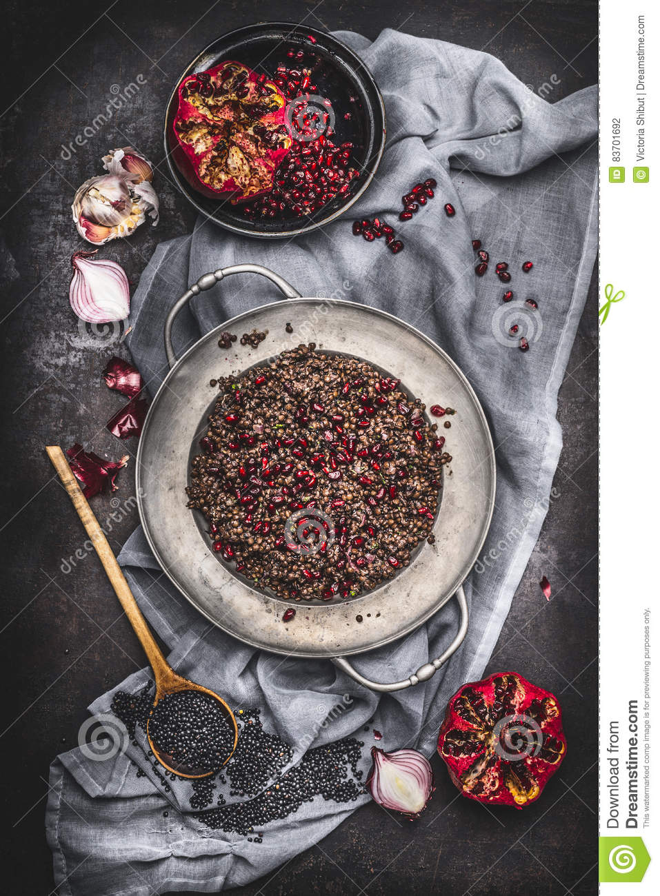 Top View Of Healthy Vegetarian Black Lentil Salad With Pomegranate And Cooking Ingredients On Dark Rustic Background With Napkin. Stock Photo