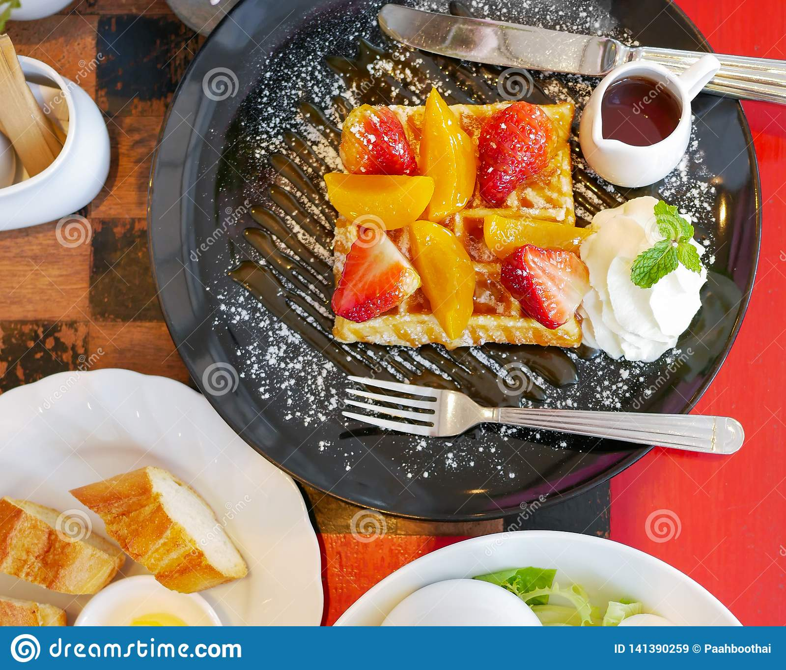 Top view of honey waffle with strawberry and peach and icing sprinkle in black plate on red table background
