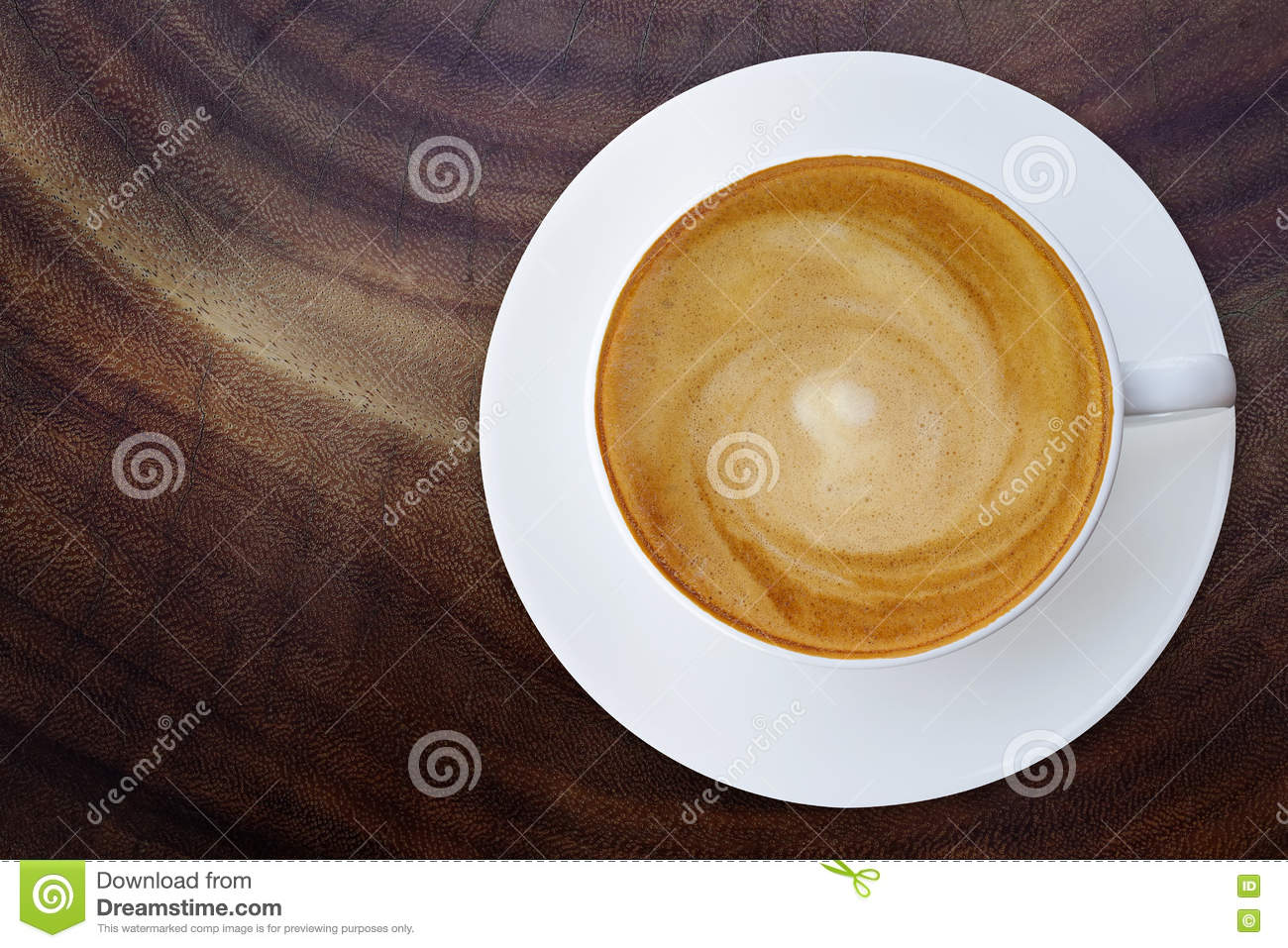 Top view of hot coffee cappuccino cup with saucer on wood texture abstract background.