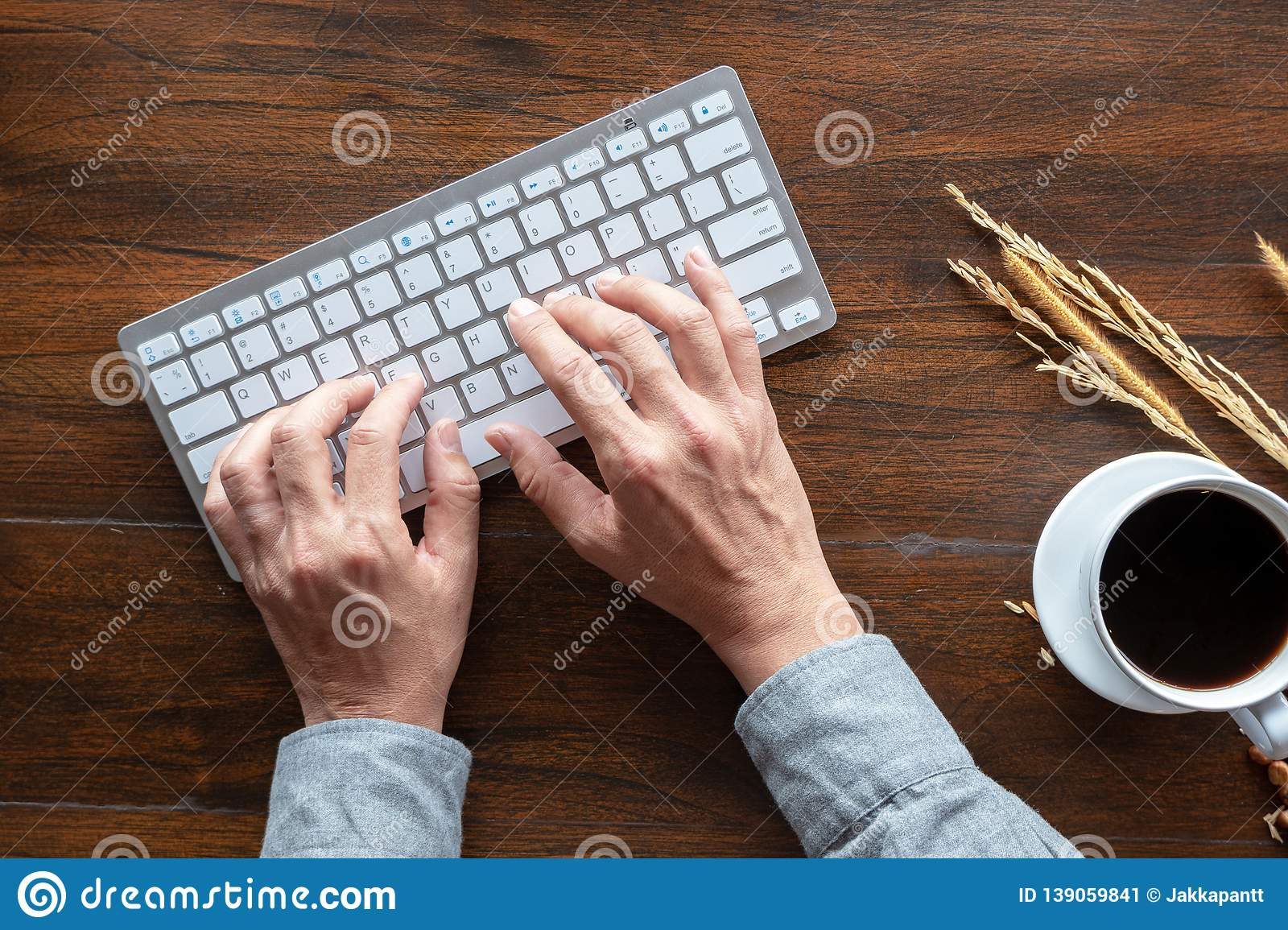 Top view of human hands typing on keyboard, wood desk