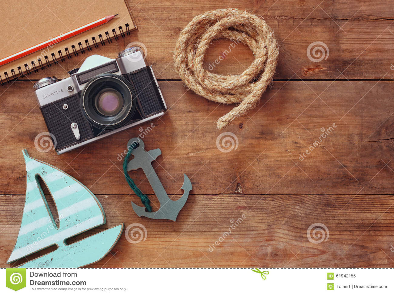 Top view image of blank notebook, wooden sailboat, nautical rope and camera. travel and adventure concept. retro filtered image