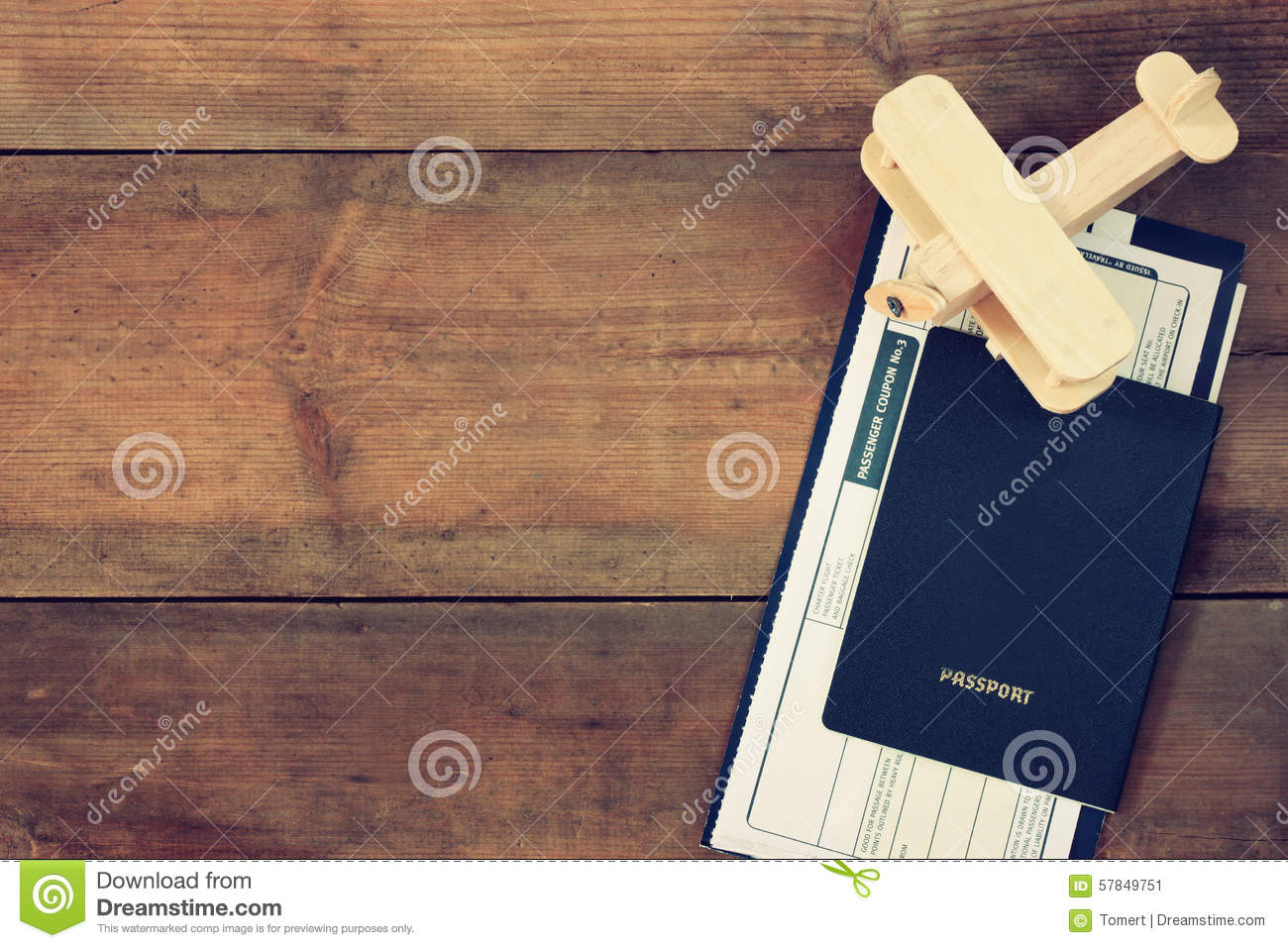 Top view image of flying ticket wooden airplane and passport over wooden table
