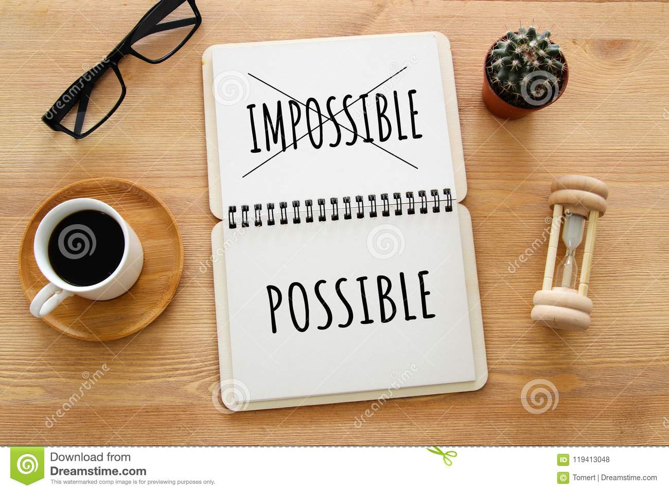 Top view image of open notebook with the text impossible, cutting the word im so it written possible. success and challenge concep