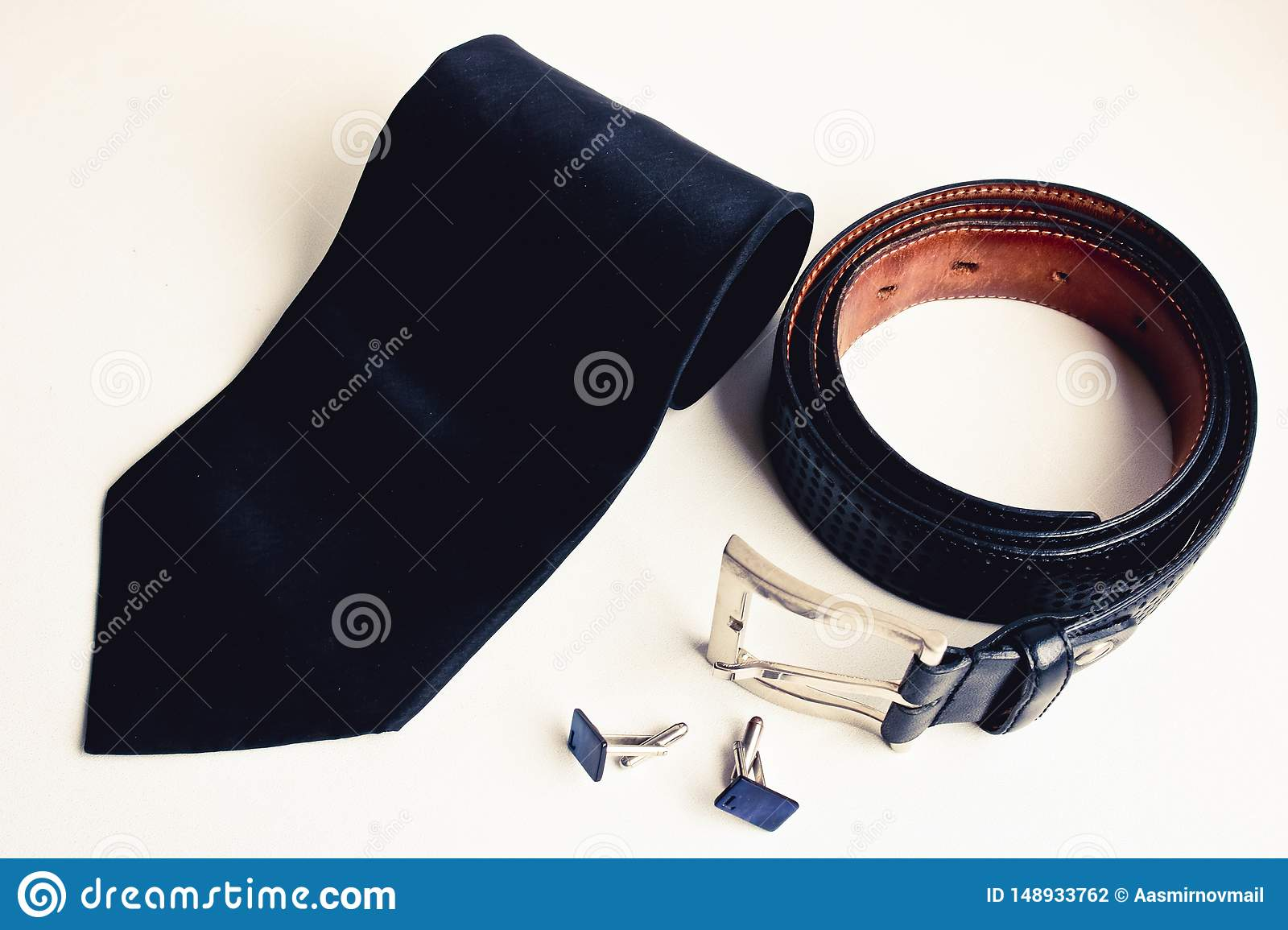 Top view of luxury men`s accessories. Black silk tie, black leather belt and cufflinks.