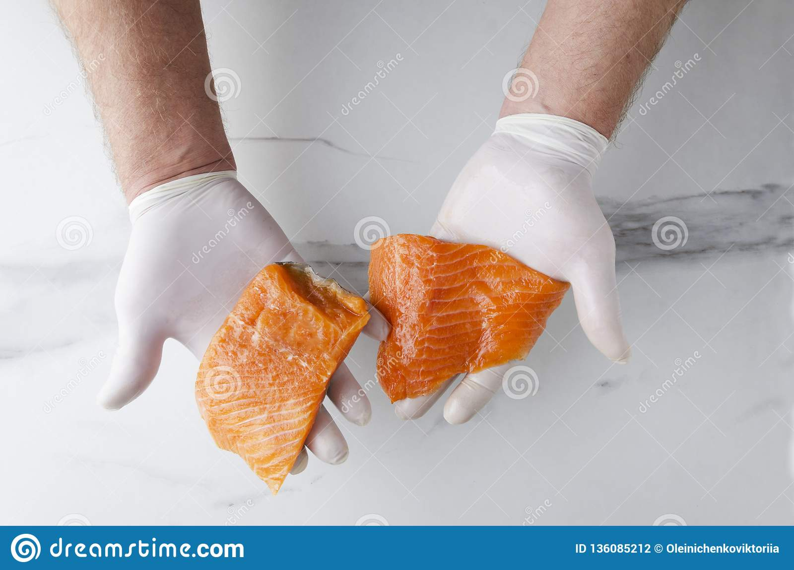 Top view of male hands and several delicious,but raw pieces of salmon against white kitchen table
