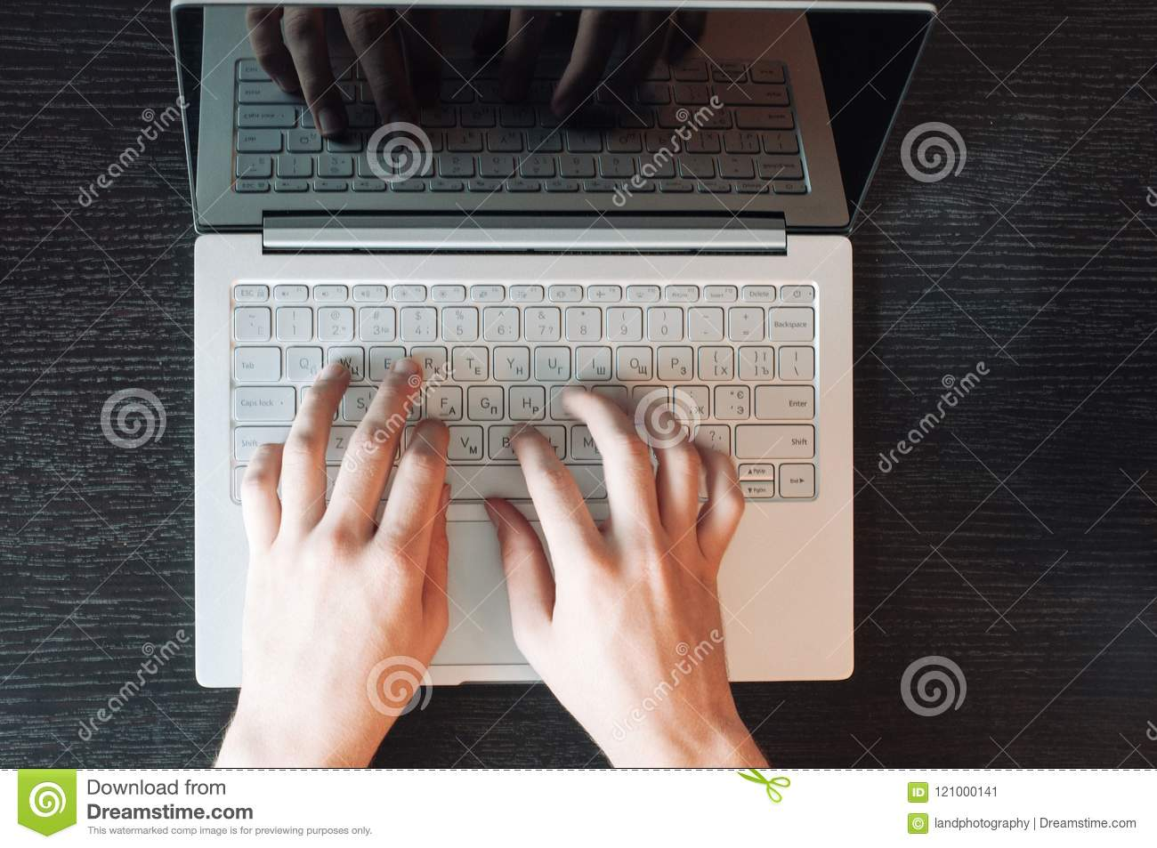 Top view of man`s hands typing on laptop keyboard