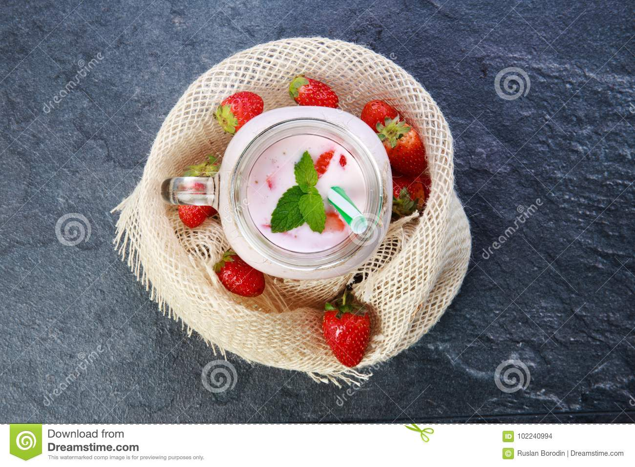A top view on a mason jar with jogurt on a marble background. Food concept.