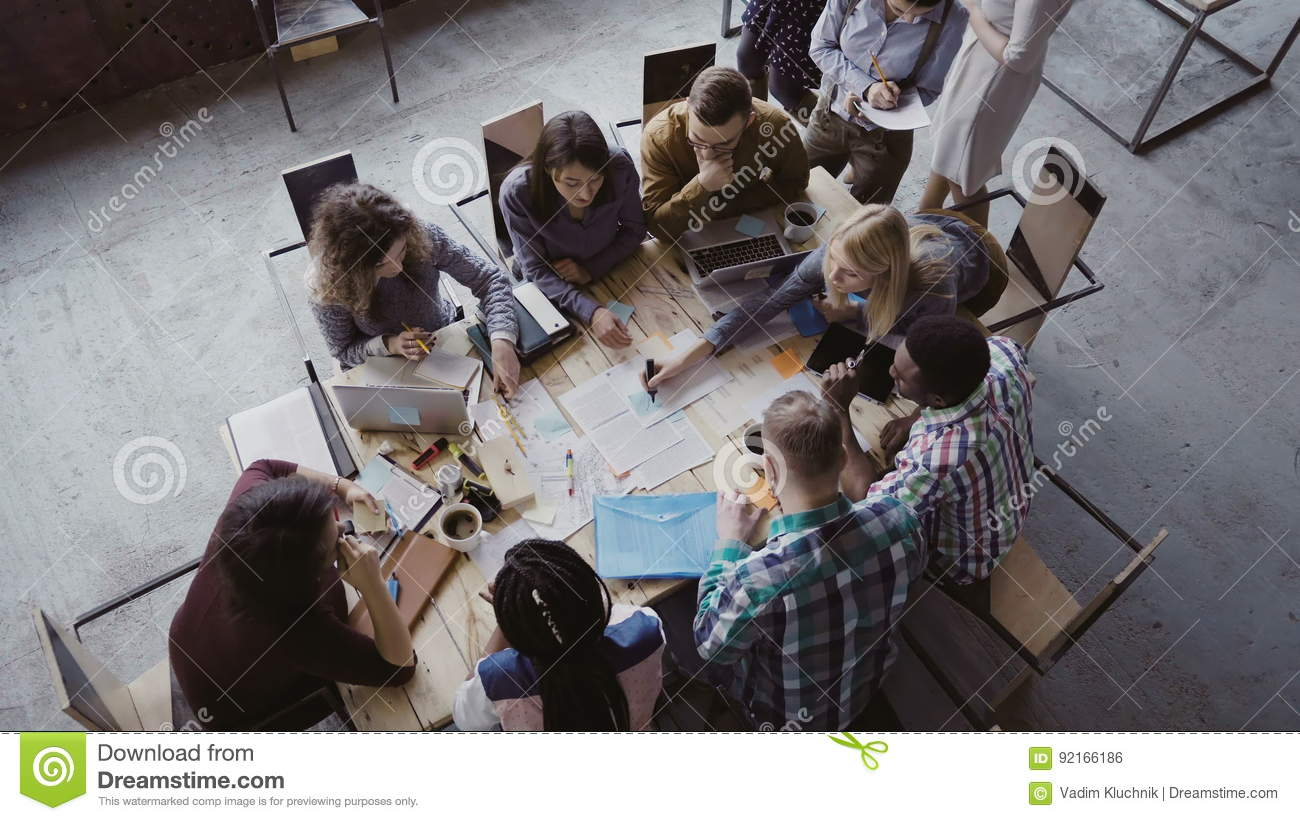 Top view of mixed race business team sitting at the table at loft office and working. Woman manager brings the document.
