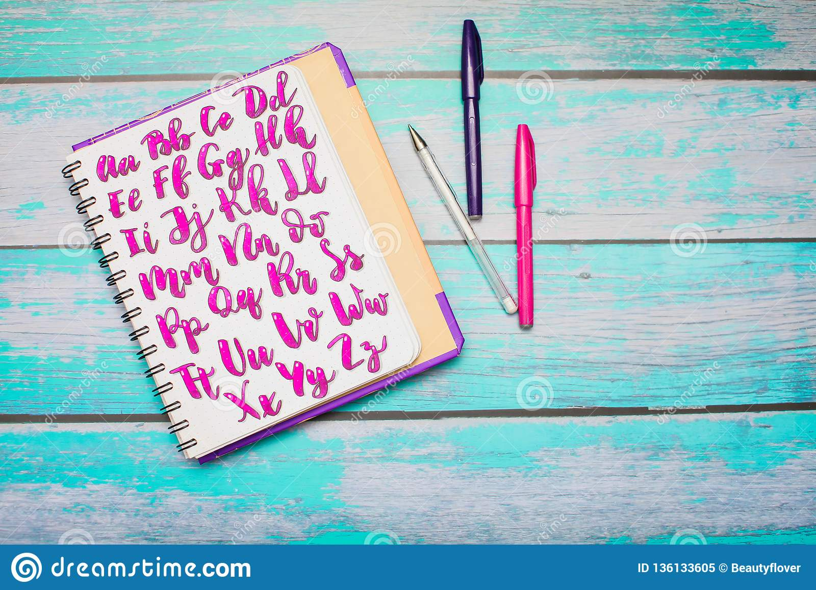 Top view of notebook with hand drawn abc alphabet letters and colorful pens on blue wooden desk background
