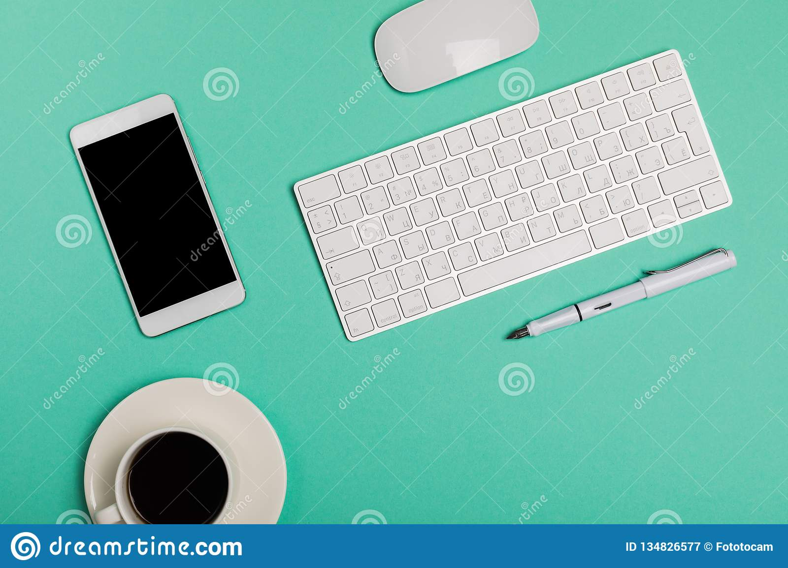 Top view of office desk workspace with smartphone, keyboard, coffee and mouse on blue background with copy space, graphic designer