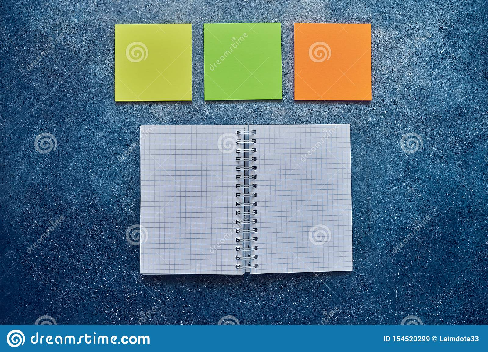 Top view of open spiral blank notebook and empty note sticker on a blue background. Back to school concept. Flat lay, copy space