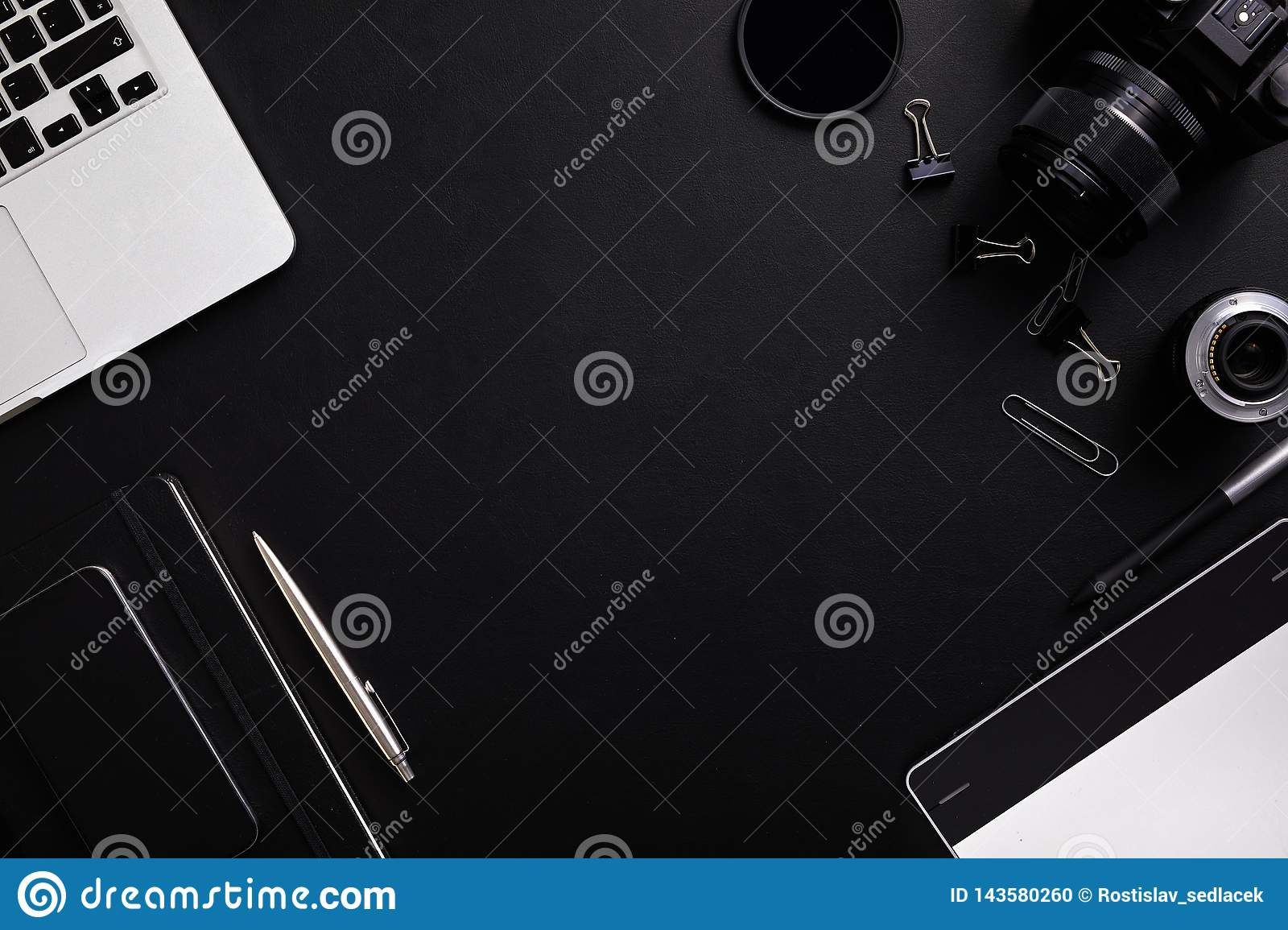 Top view of photographer table with latptop, camera, lenses and diary with copy space