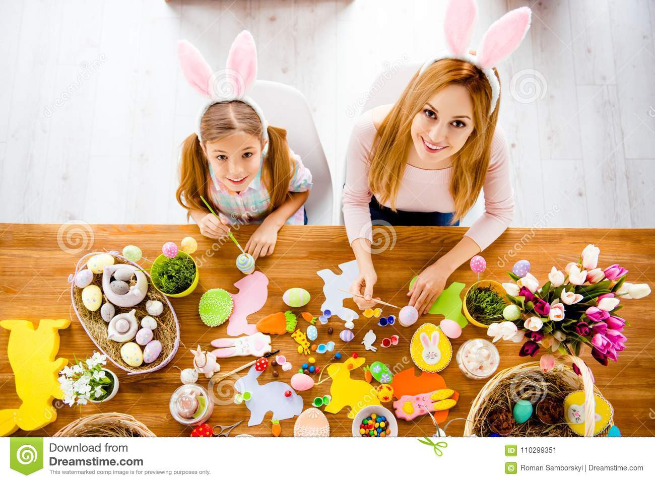 Top view of pretty beautiful mummy teaching her cute joyful small daughter paint decorate easter eggs together wearing rabbit cos