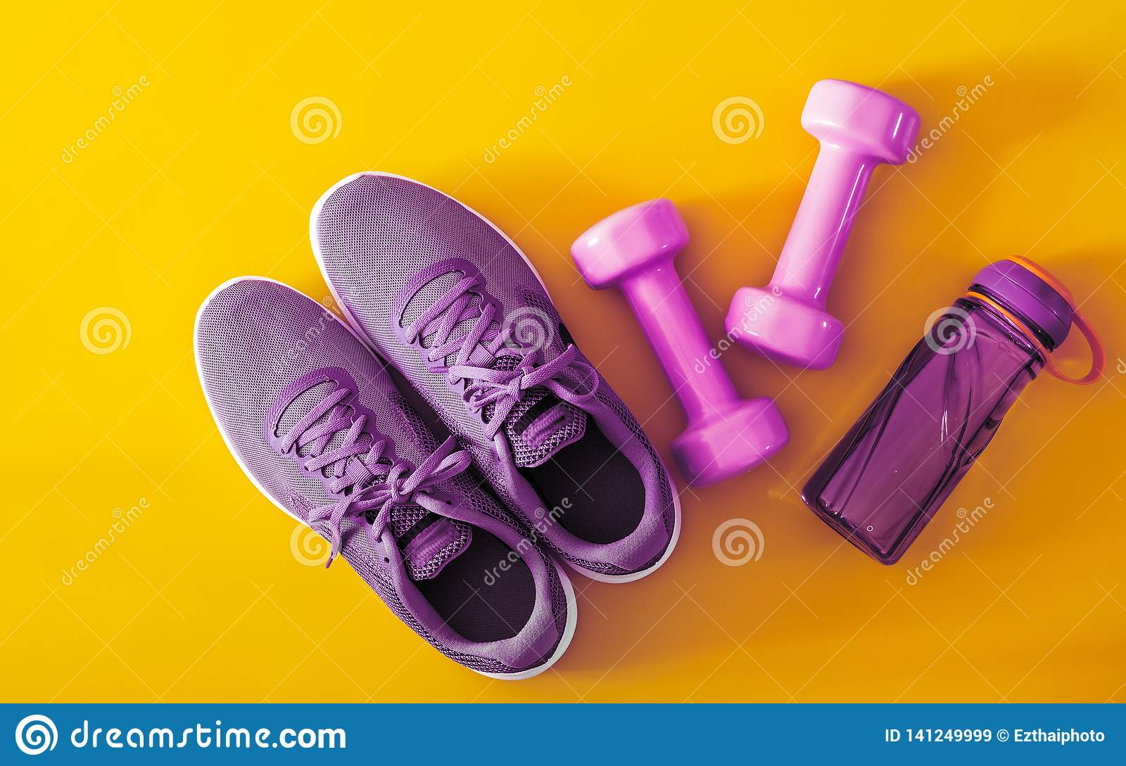 Top view of purple and violet sport shoes, dumbbells and bottle of water on yellow background. Fitness and Healthy lifestyle
