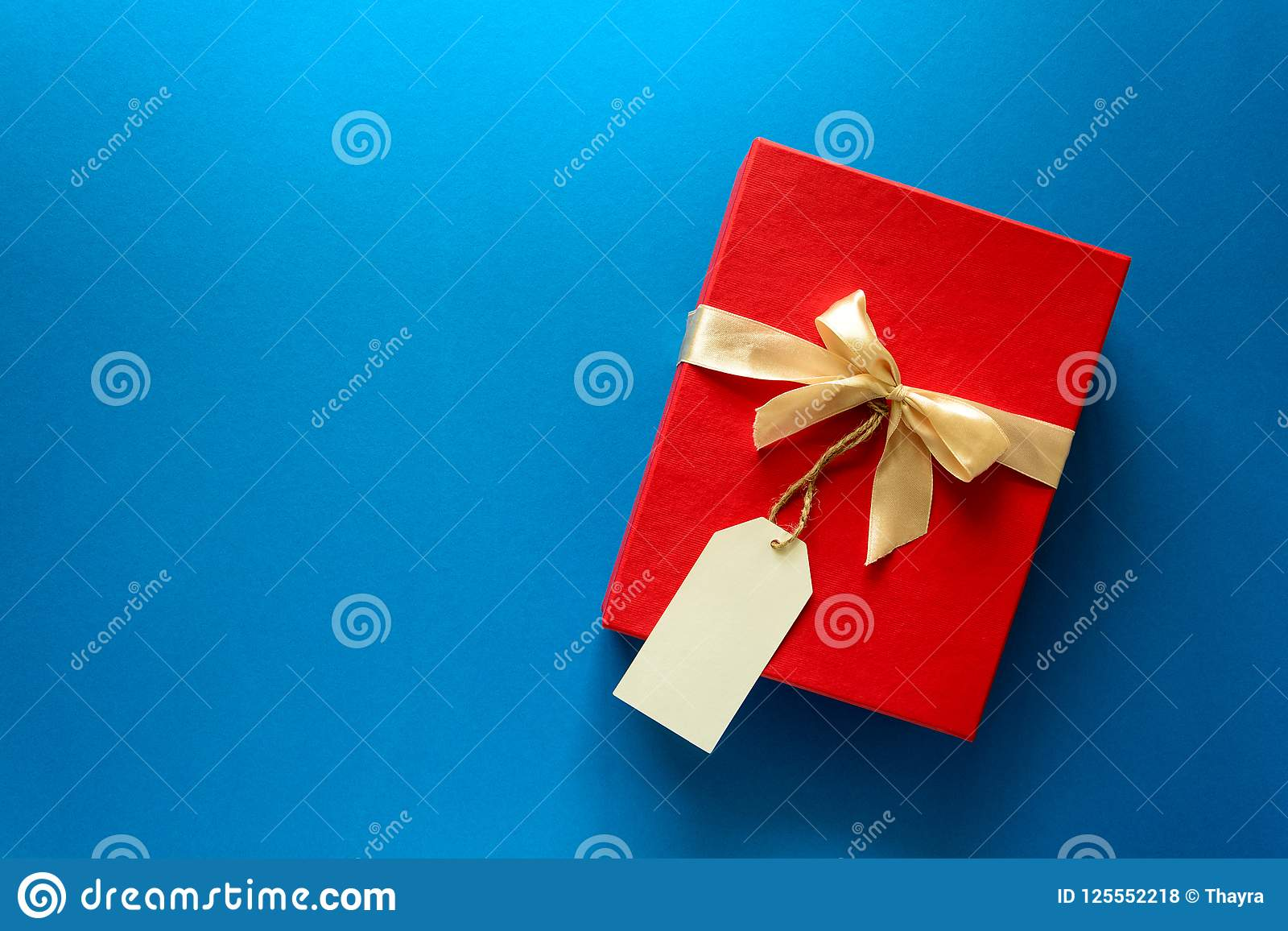 Top view on red Christmas gift box decorated with ribbon on blue paper background.