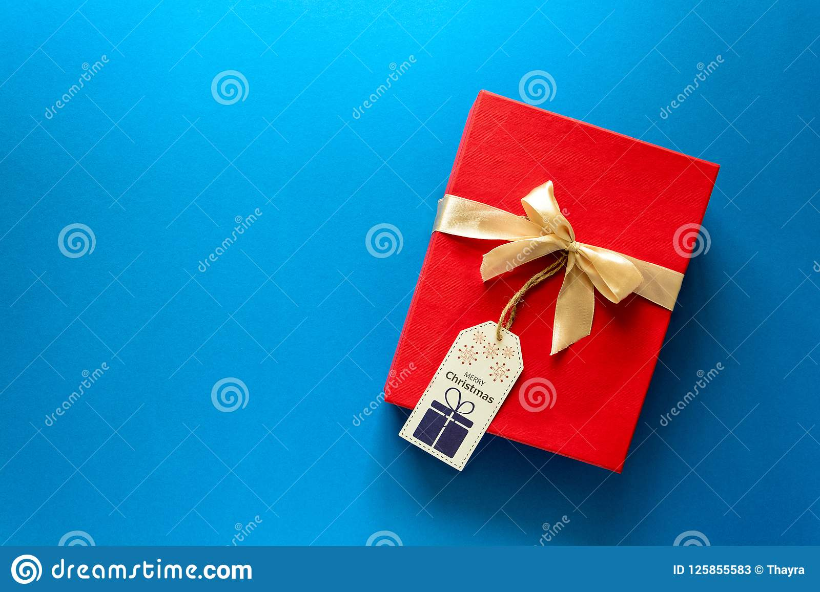 Top view on red Christmas gift box decorated with ribbon on blue paper background. New Year, holidays and celebration decorations