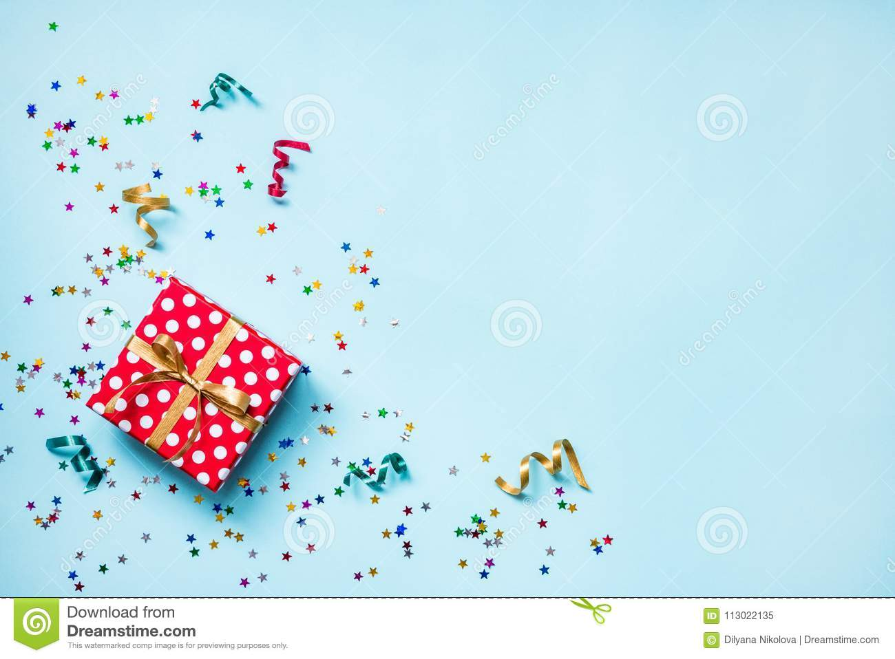 Top view of a red dotted gift box, scattered glittering star shaped confetti and colorful ribbons over blue background. Celebratio