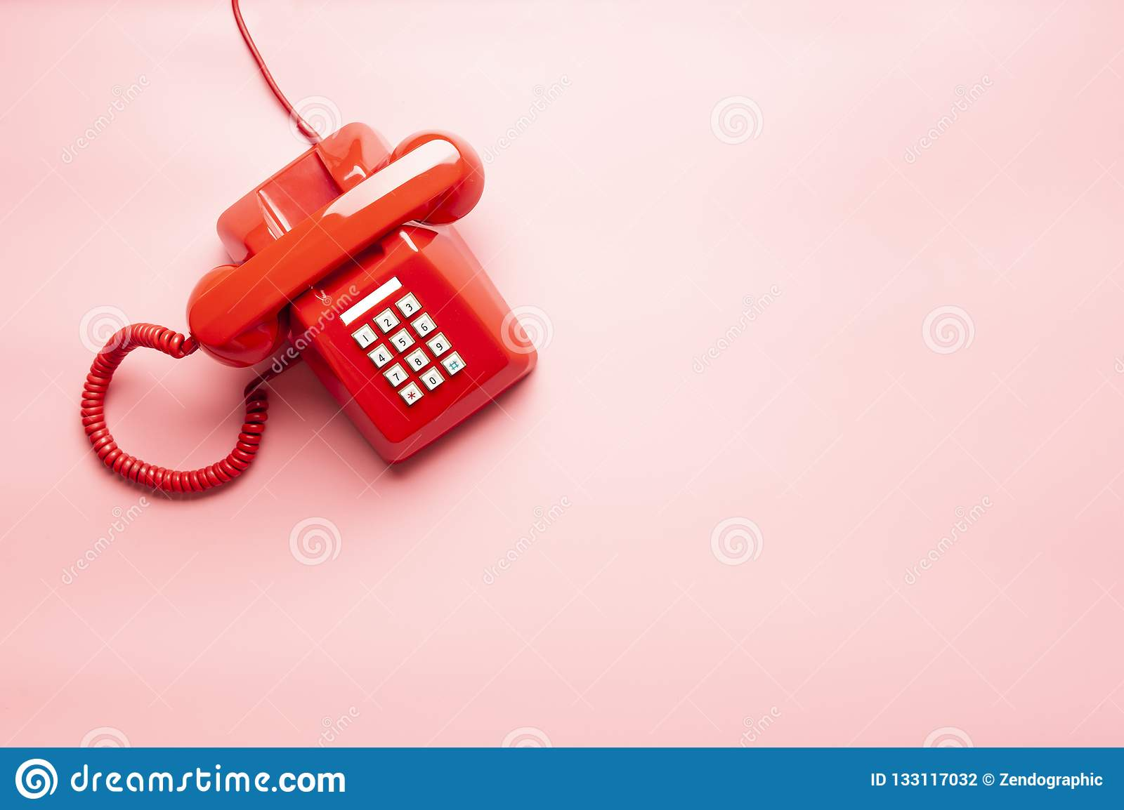 Red telephone on pink desk