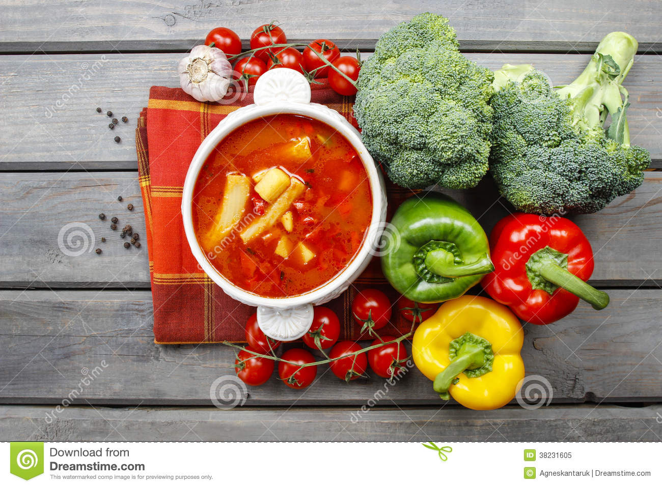 Top view of red tomato soup on wooden table. Fresh vegetables ar