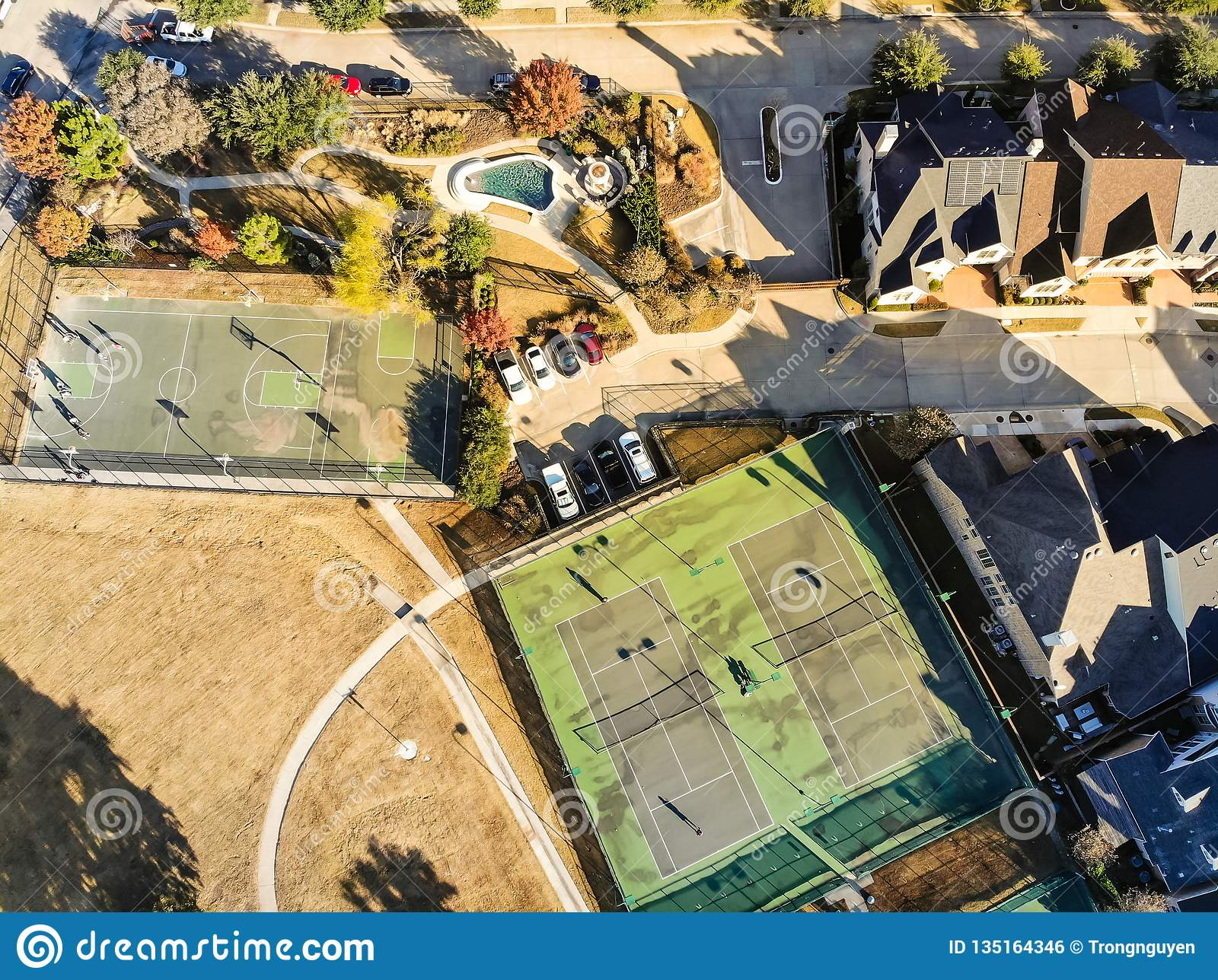 Top view residential tennis courts with players at autumn morning in North Texas, America