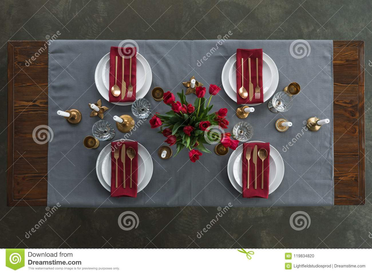 top view of rustic table setting with red tulips bouquet, tarnished cutlery, wine glasses, candles and empty plates on tabletop