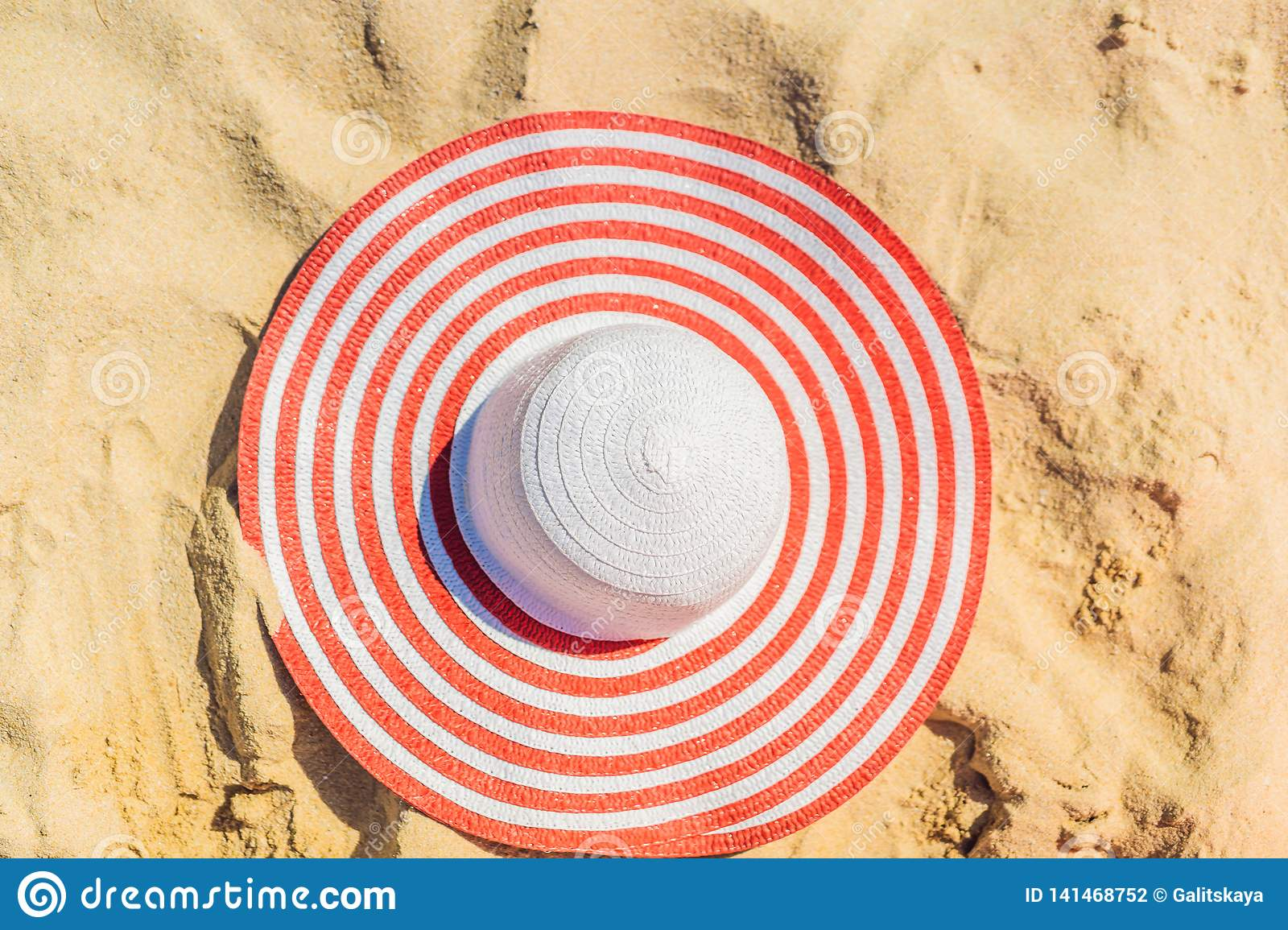 Top view of sandy beach with red striped beach hat Background with copy space and visible sand texture