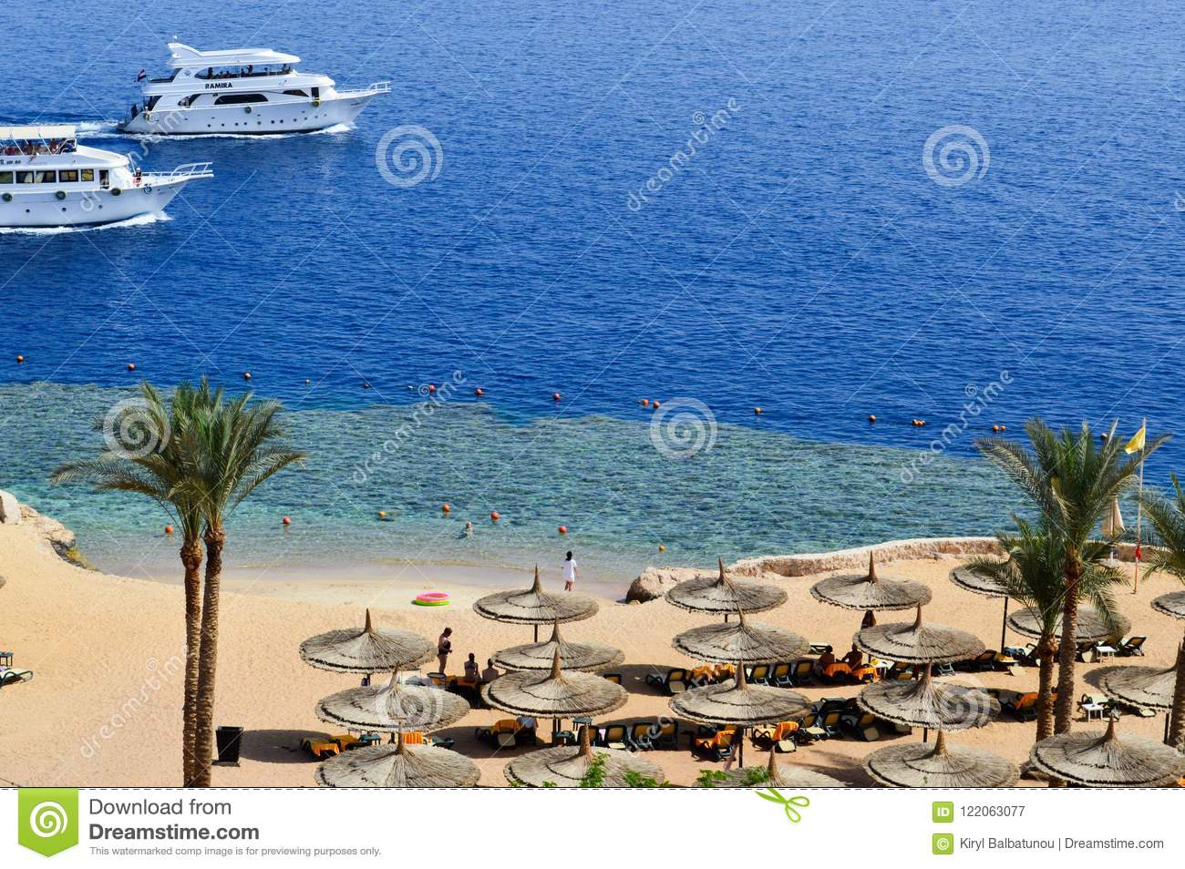 Top view of a sandy beach with sunbeds and sun umbrellas and two large white ships, a boat, a cruise liner floating in the sea on