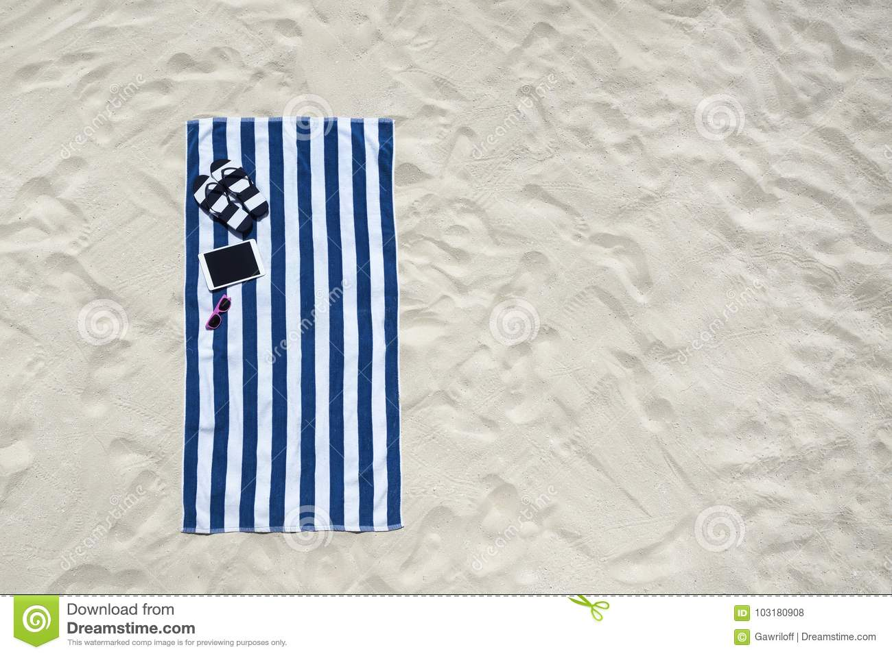 Top view of sandy beach with towel frame and summer accessories.