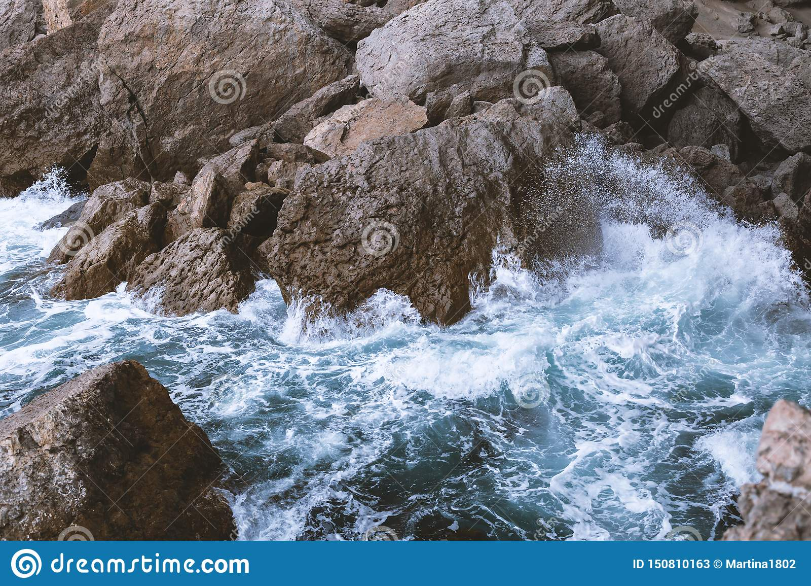 Top view of the sea waves that beat on the rocky coast