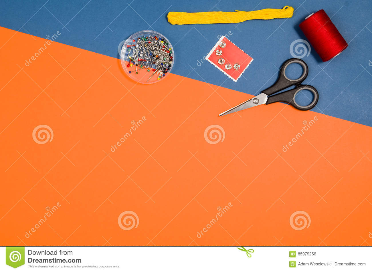 Top view of sewing or knitting accessories over blue background